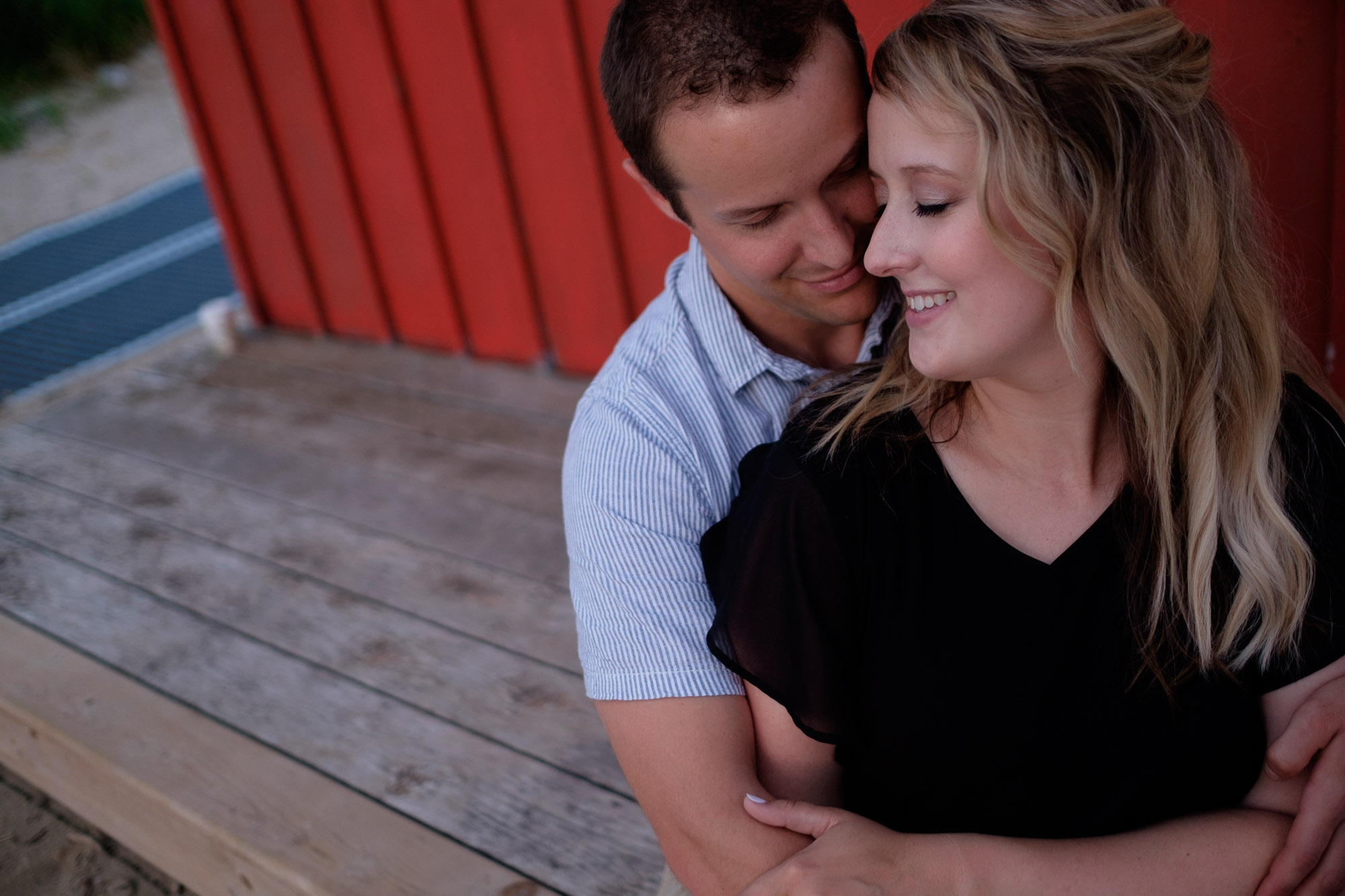 Alex + Colton embrace in front of a beach hut during their waterfront engagement portrait session in Goderich, Ontario on the shores of Lake Huron.