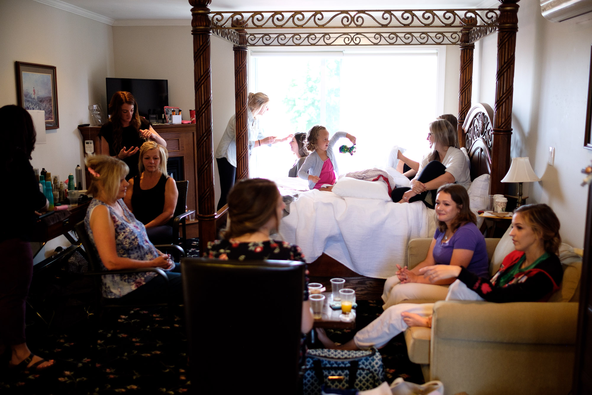 A crowded room as the girls get ready in a suite at the Hessenland Inn for Alex + Colton's wedding.