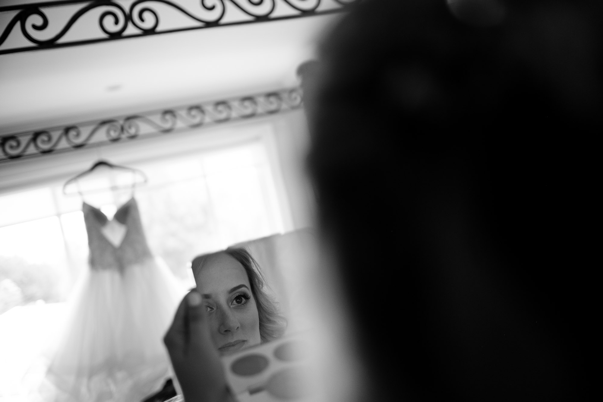 Alex checks her makeup with her wedding dress in the background in this candid black and white wedding photograph.