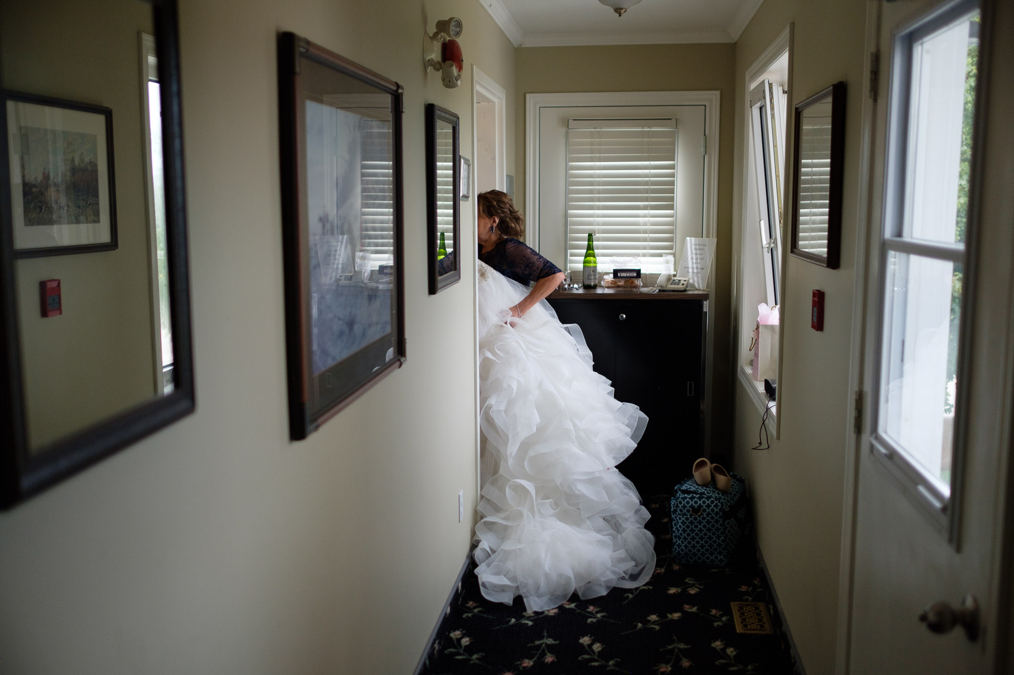 The wedding dress is moved to the getting ready suite at the Hessenland Inn before Alex + Colton's outdoor wedding ceremony.