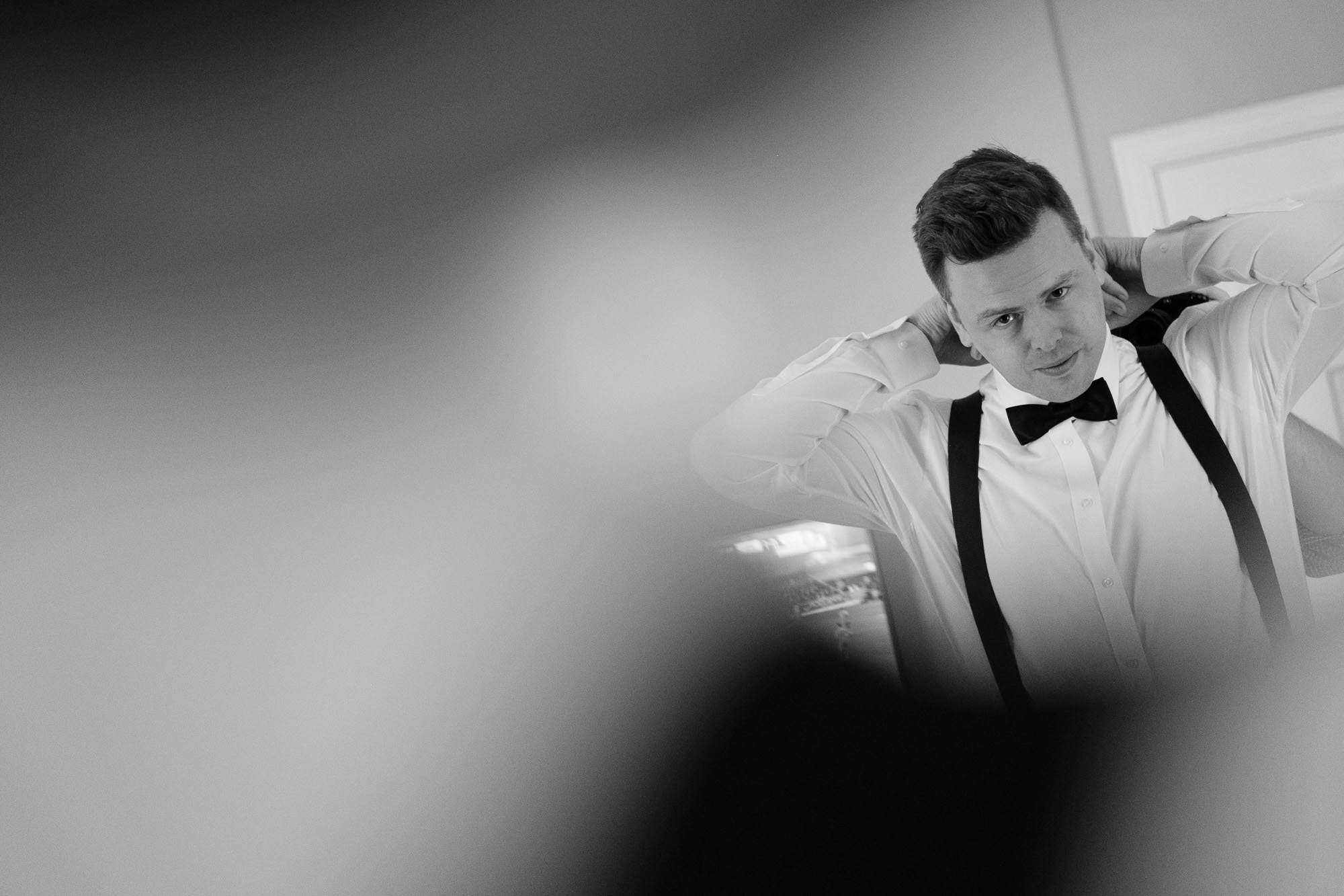The groom adjusts his bowtie while getting ready for his wedding at the King Edward Hotel in Toronto.