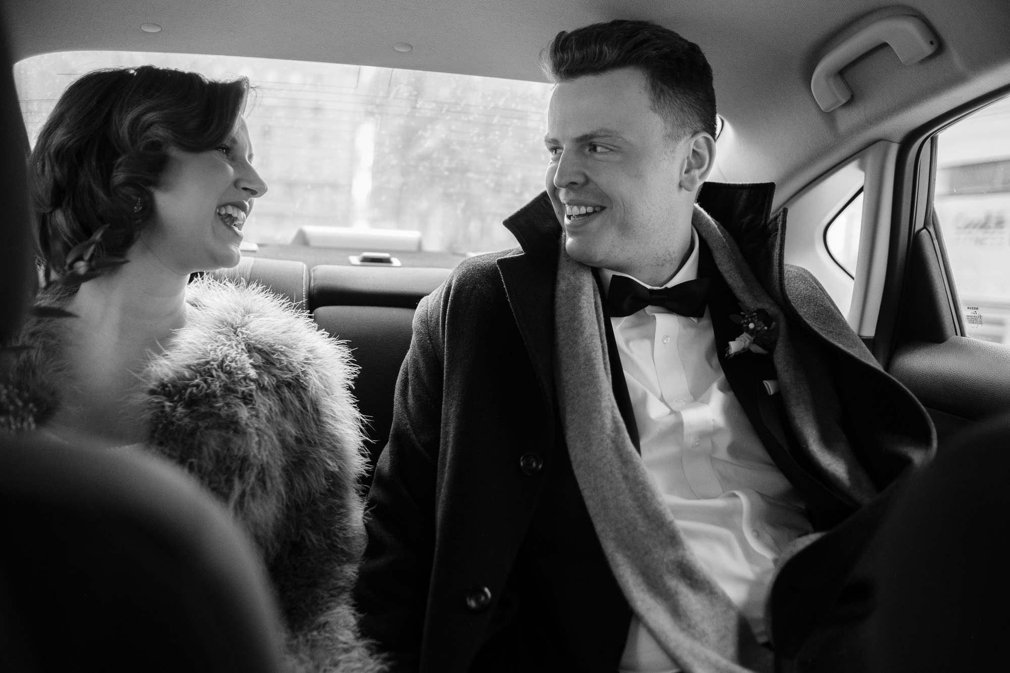 the bride and groom share a laugh in an Uber while traveling to through Toronto before their winter wedding at the Enoch Turner schoolhouse.