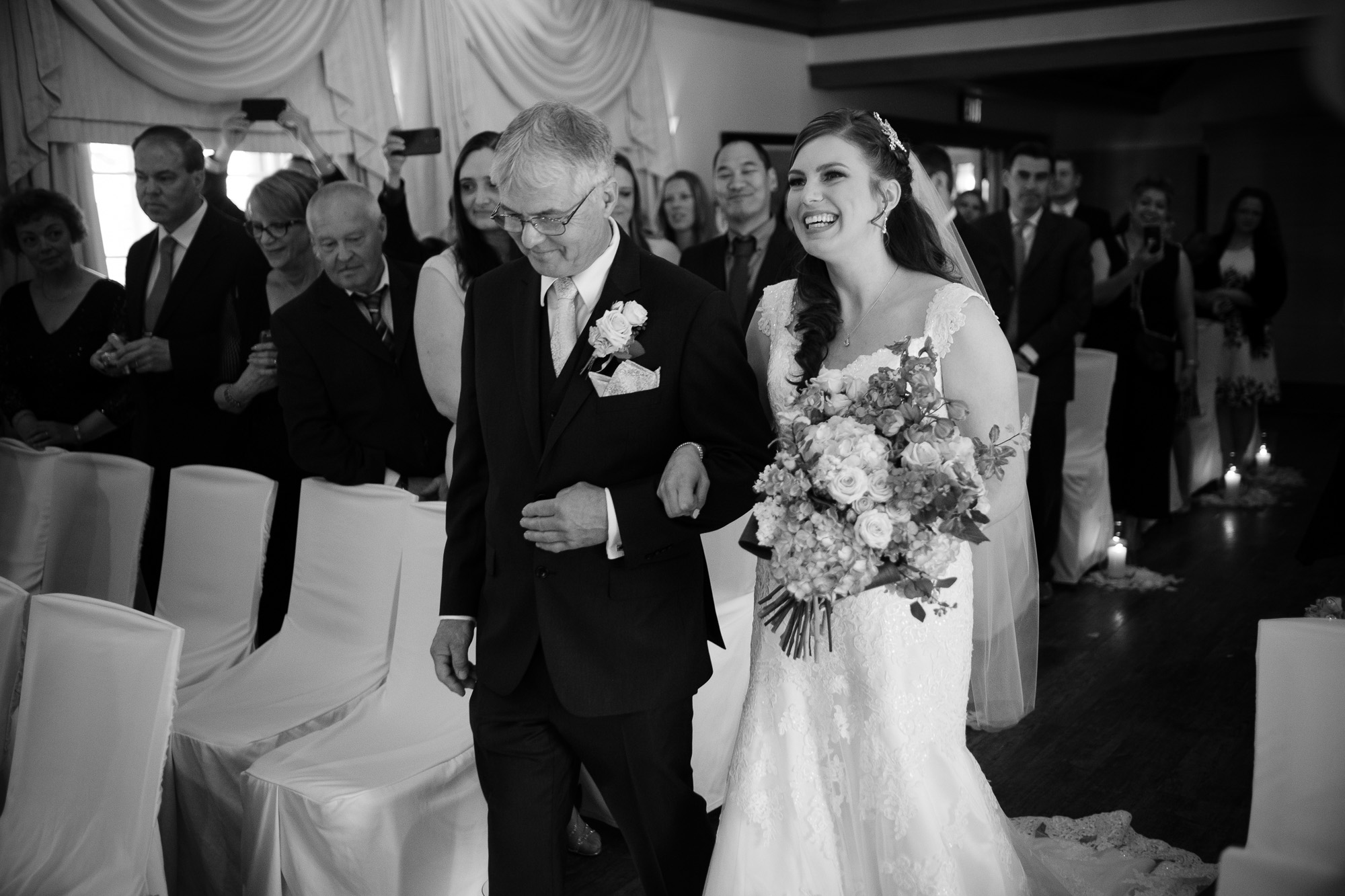 The bride is escorted down the aisle by her father in the this black and white wedding photograph from a wedding ceremony at the Glenerin Inn just outside of Toronto.