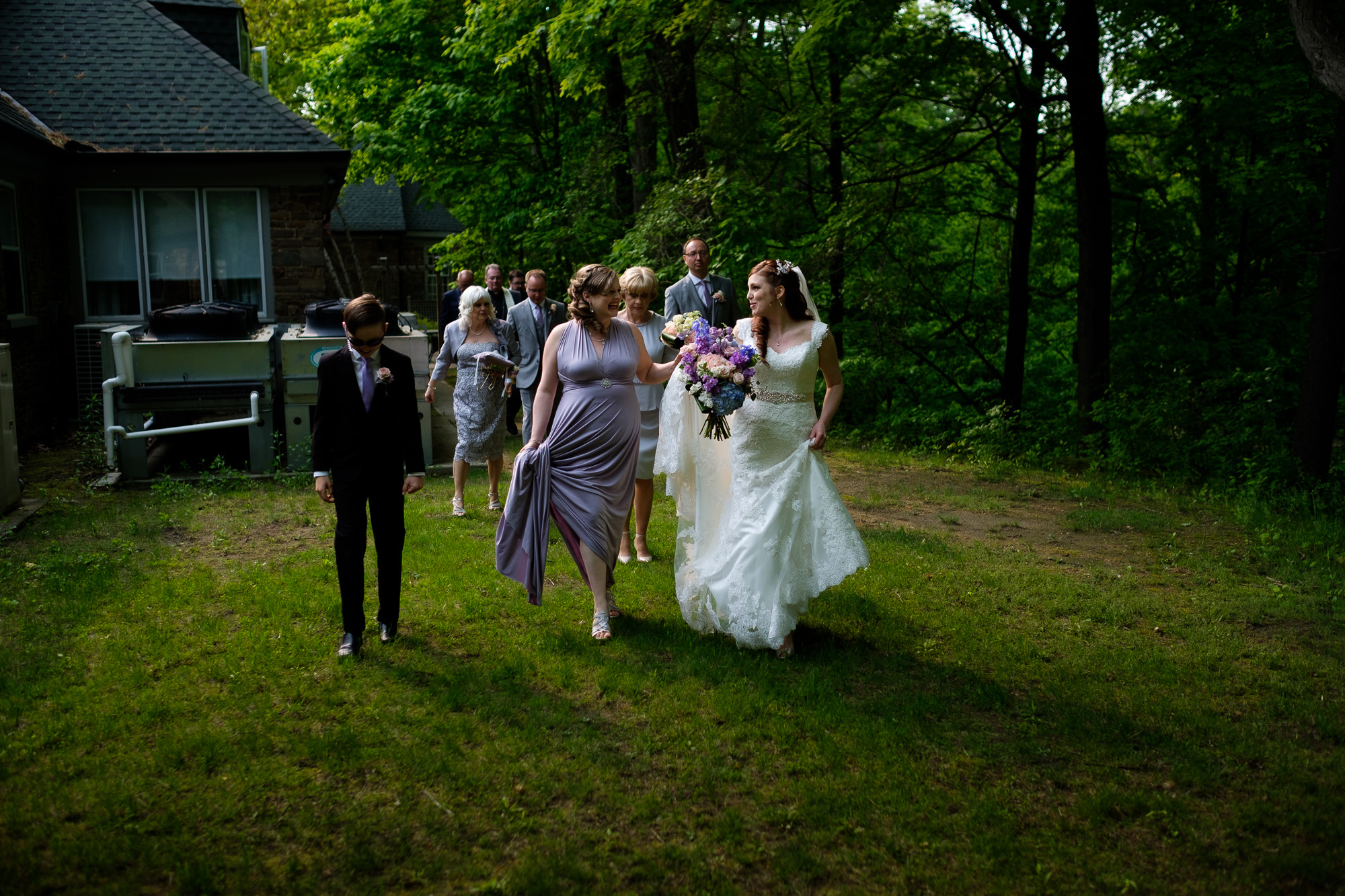 The bride leads her family and friends to the wedding portrait location after the wedding ceremony at the Glenerin Inn just outside of Toronto, ontario.