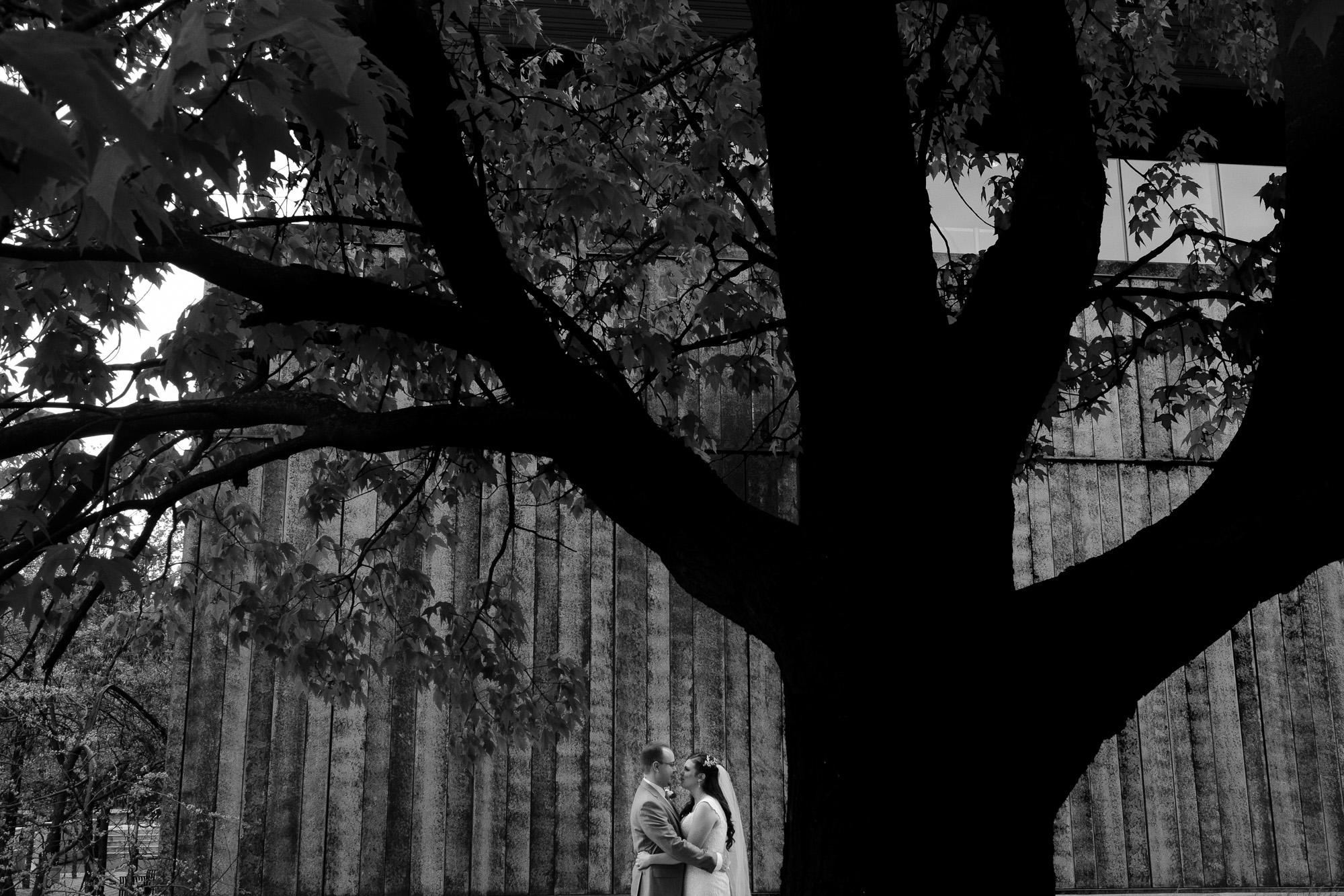 Cheri + Chris pose for a black and white wedding portrait on the grounds of University of Toronto Mississauga after their wedding ceremony at the Glenerin Inn.