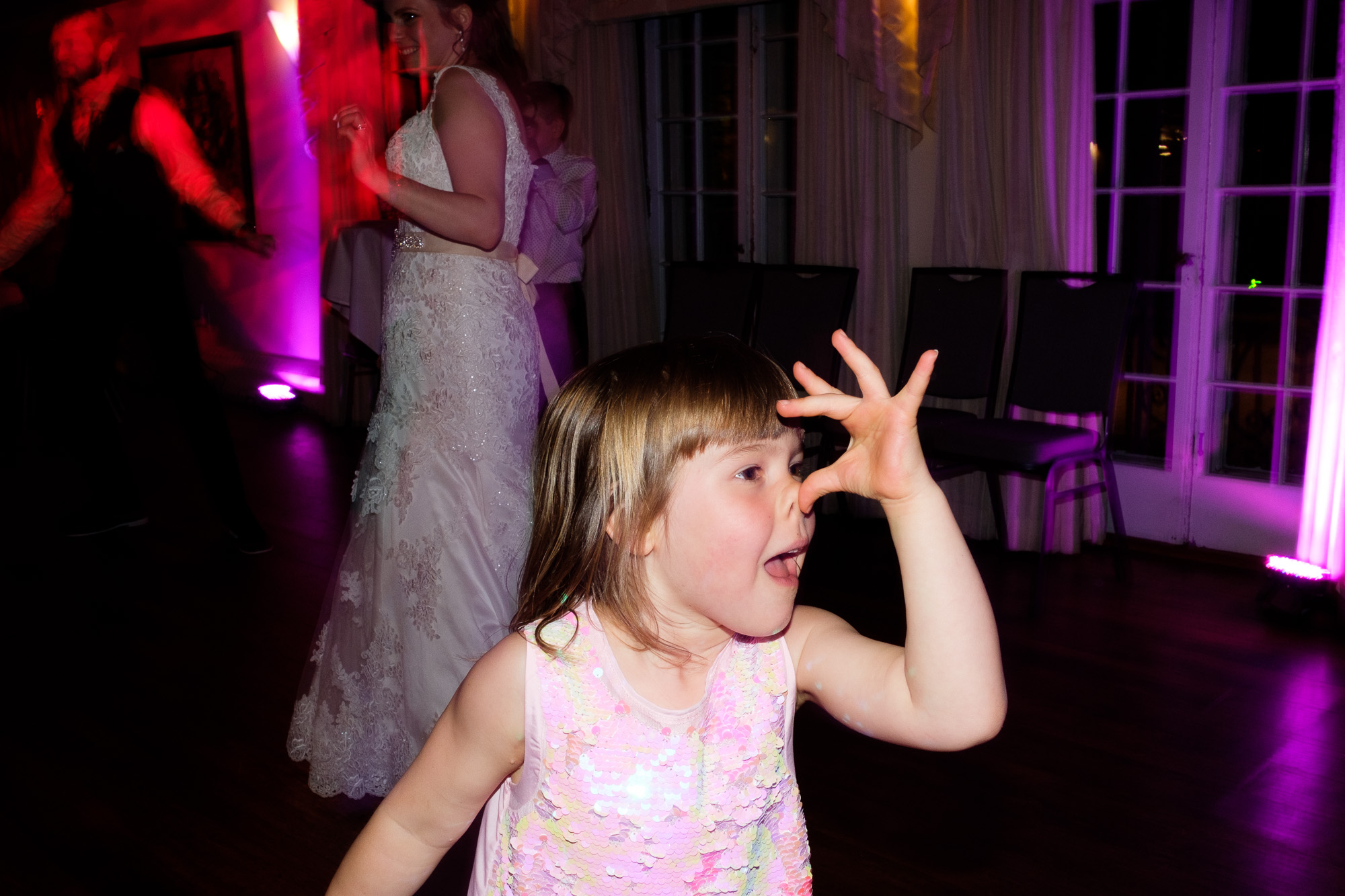 The flower girl hams it up on the dance floor late into the night during the wedding reception at the Glenerin Inn outside of Toronto.