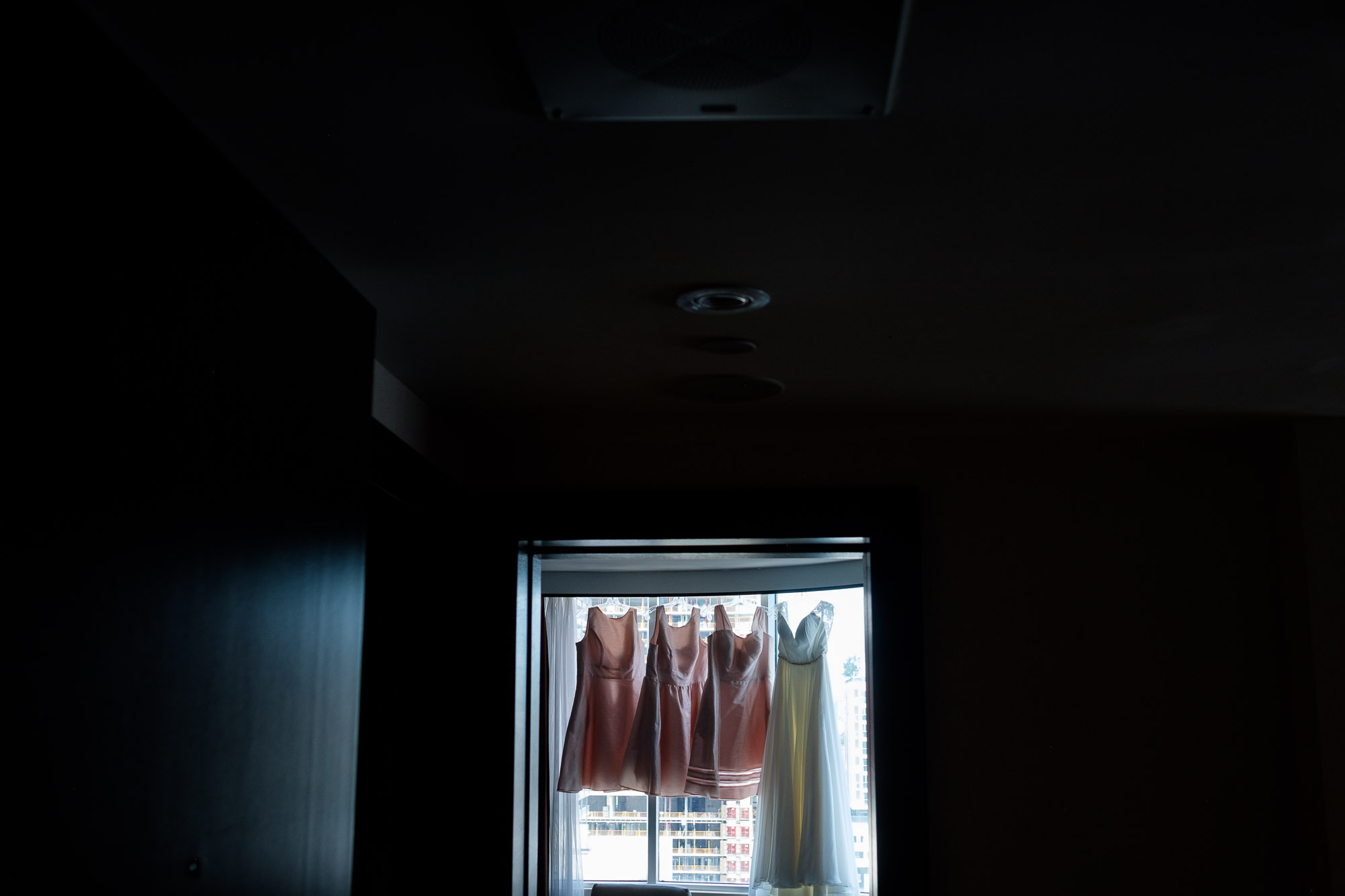 A wedding detail photograph of the brides and bridesmaid dresses hanging up in Katherine's suite at the Hyatt Toronto.