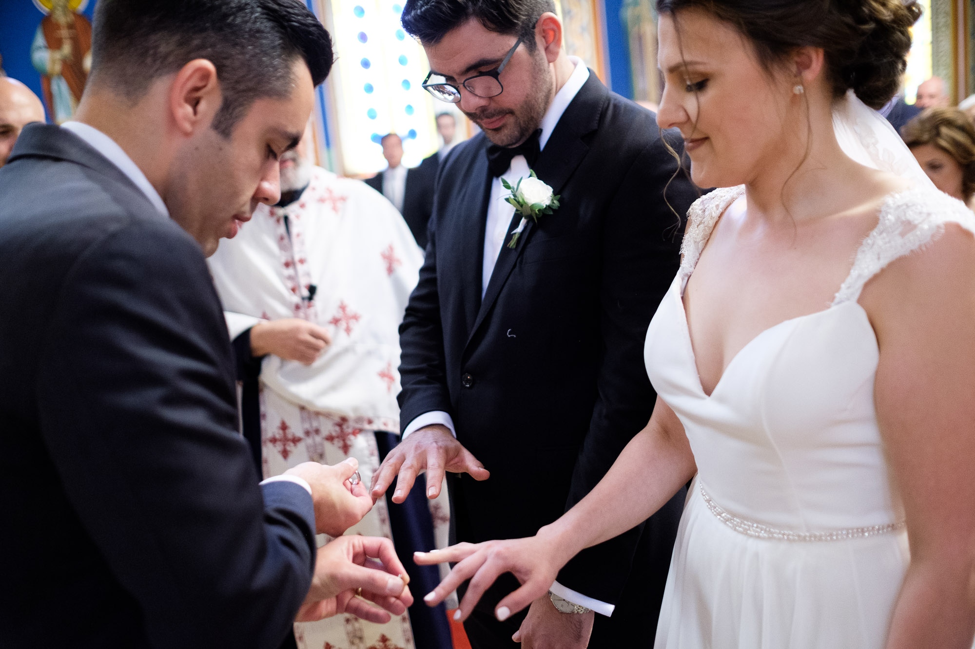 The best man exchanges the bride and grooms wedding rings during their Greek Orthodox wedding ceremony at St. Georges Greek Orthodox Church in Toronto.