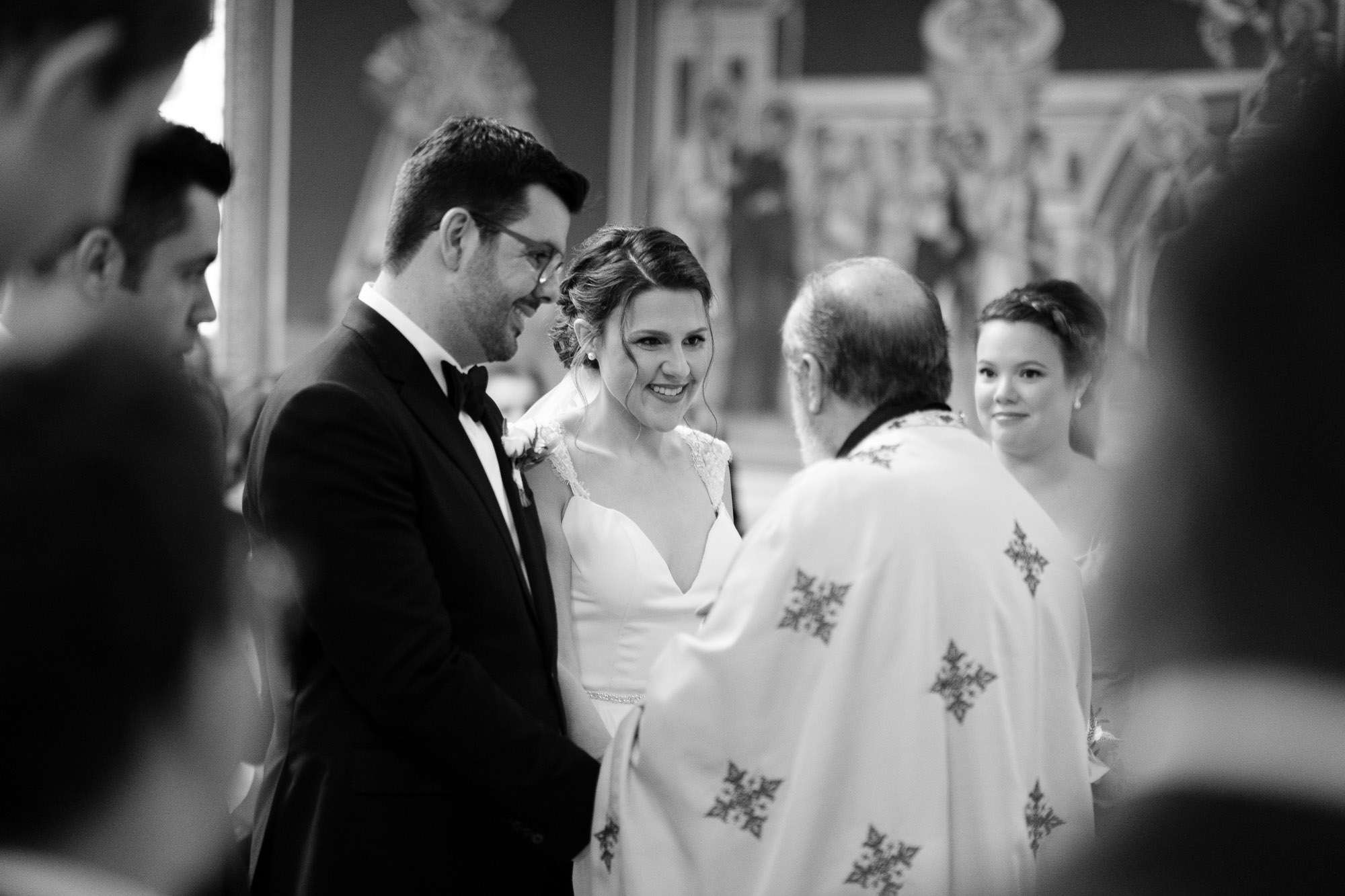 Katherine + Kosta exchange a laugh during their Greek Orthodox wedding ceremony at St. George's Greek Orthodox Church in Toronto.