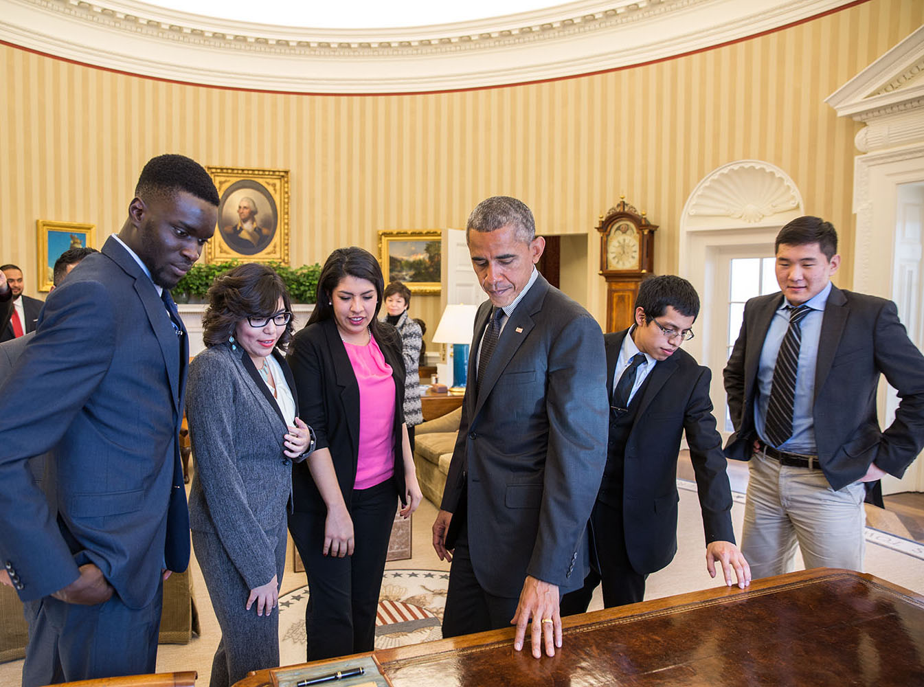 President Barack Obama shows the Resolute Desk to young immigrants while giving them an Oval Office tour. The President met with the group of DREAMers, who talked about how they have benefited from Deferred Action for Childhood Arrivals, Feb. 4, 2015. (Official White House Photo by Pete Souza)