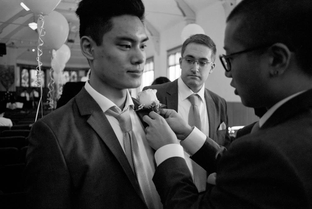 The best man helps out one of the groomsmen.