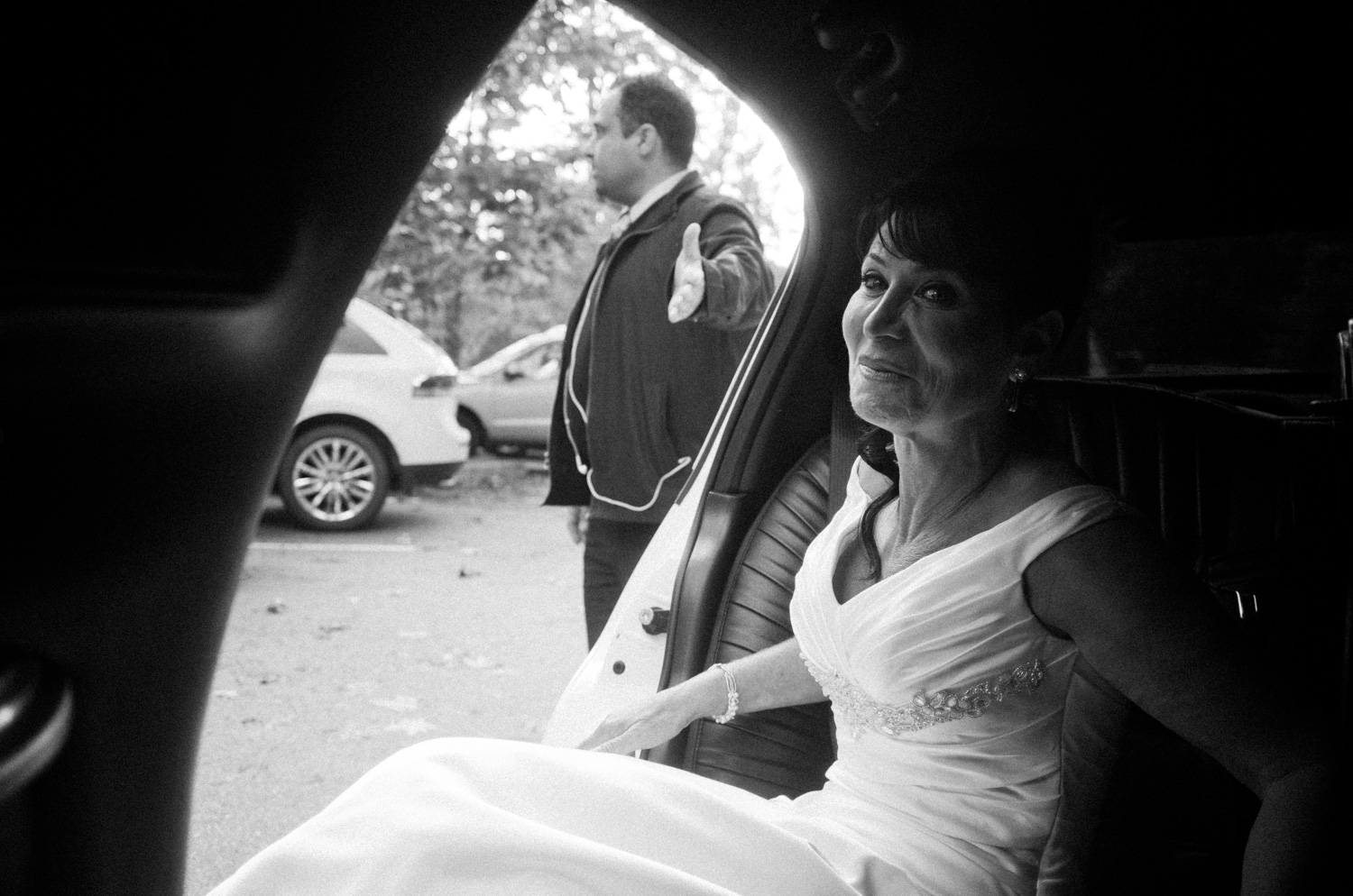 As the bride was getting out of the limousine, I saw this moment come together very quickly. I took two quick frames and this was the better of the two compositionally and also the expression of the bride. She was looking just behind me to the bridesmaids.