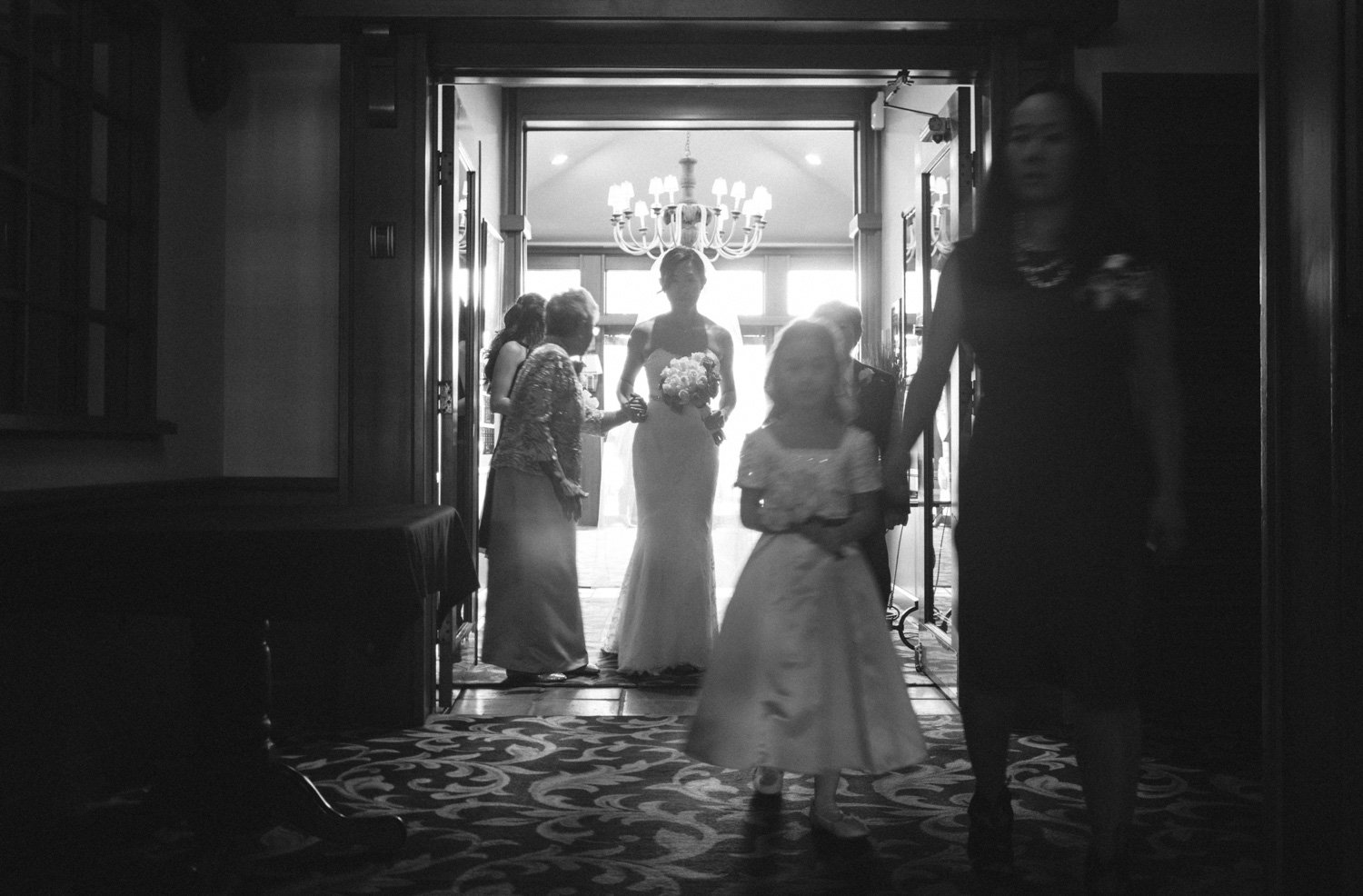 In some scenes I photograph, there can be a few things going on. I intentionally keep all these elements in the photograph to give a broader view of what happened on a particular wedding day. I see the mother of the bride holding the bride's hand while the flower girl is led by her mother (?).