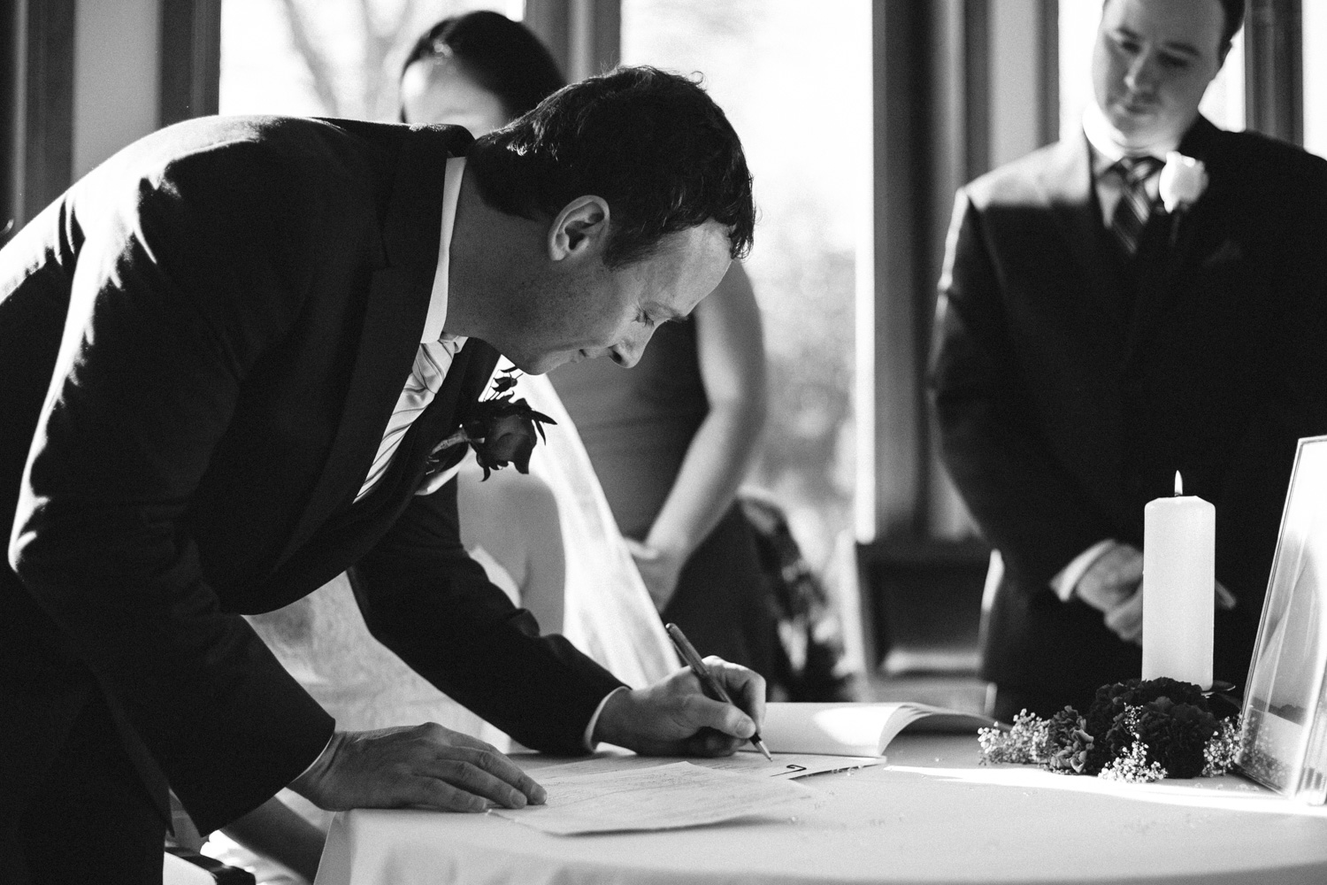 I saw the groom crack this smile as he was signing the wedding papers and quickly grabbed the moment. Just a millisecond prior he was not smiling. The smile really made this photograph.