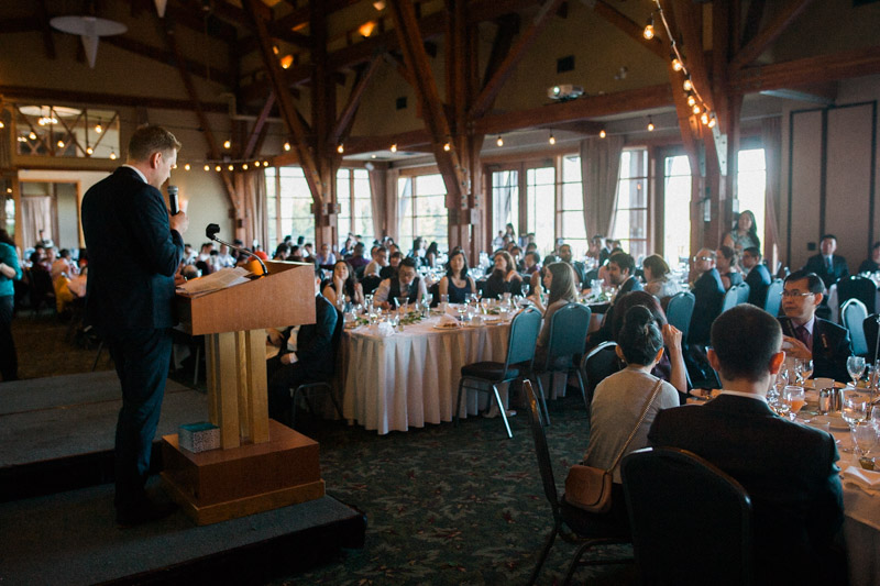 A groomsman gives a heart-felt speech while reception guests look on.