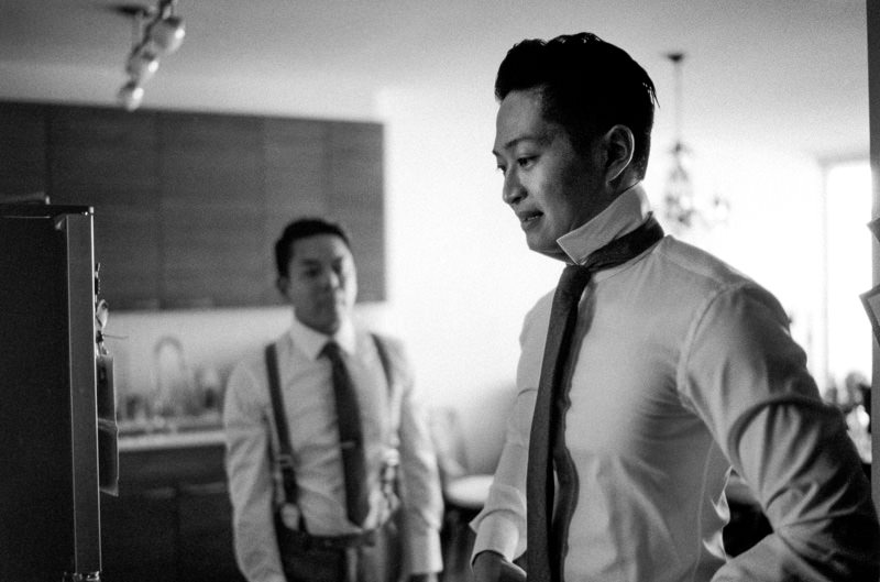 The groom looks into a mirror to check his shirt.