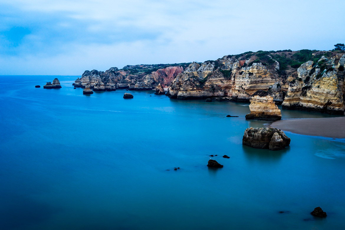 The calm waters of Praia Dona Ana before the sun rises in Lagos, Portugal.