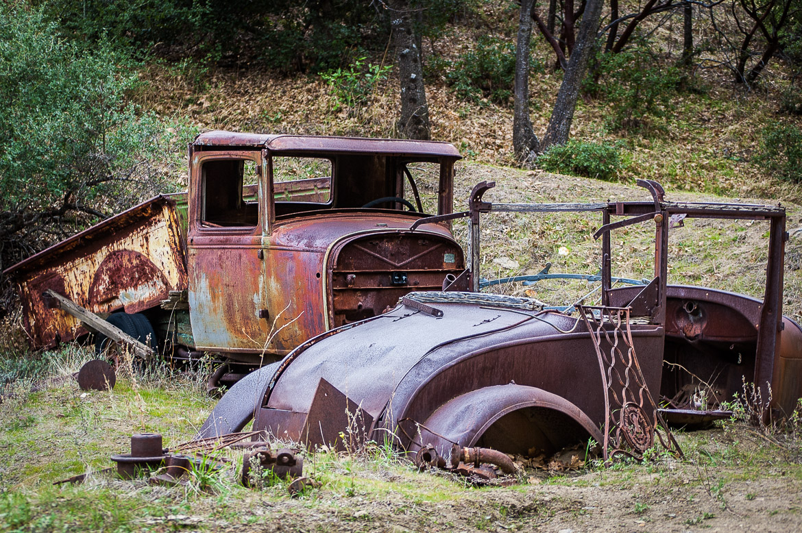 The earth swallows what remains of these old car bodies near Eagle Mine in Julian, California.