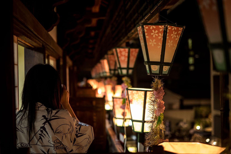 La vista dai terrazzi delle terme, con una cliente in yukata intenta a fotografare la vista.