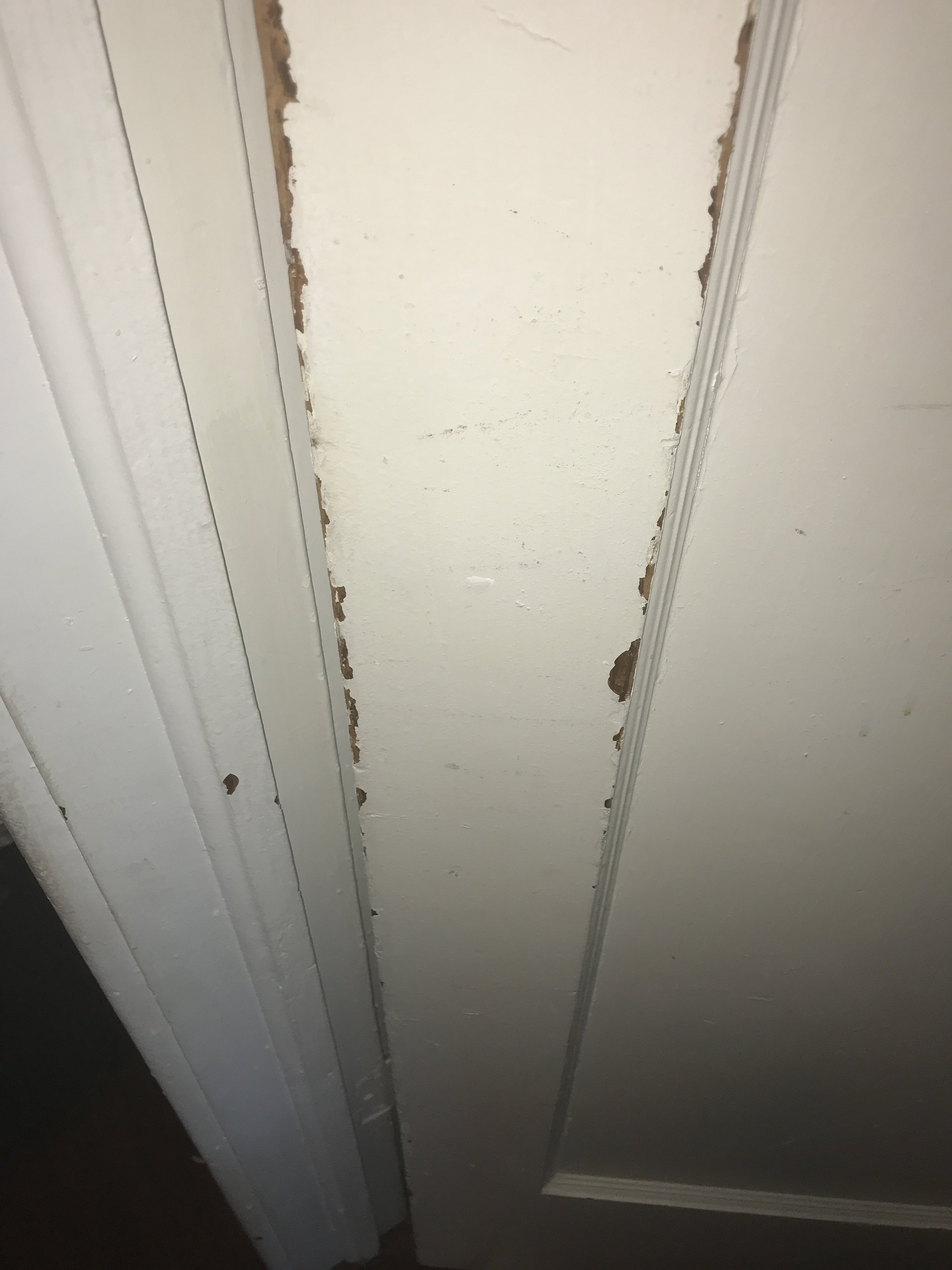 Latex paint has chipped off of the stiles on this interior door. The paint was applied directly over the existing oil based varnish.