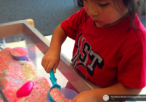 Elias works in the sensory table with colored rice and ice cream themed tools