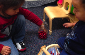 Elias and Dallas add more beads to the curved mirror. They took great delight in taking turns rocking the beads back and forth