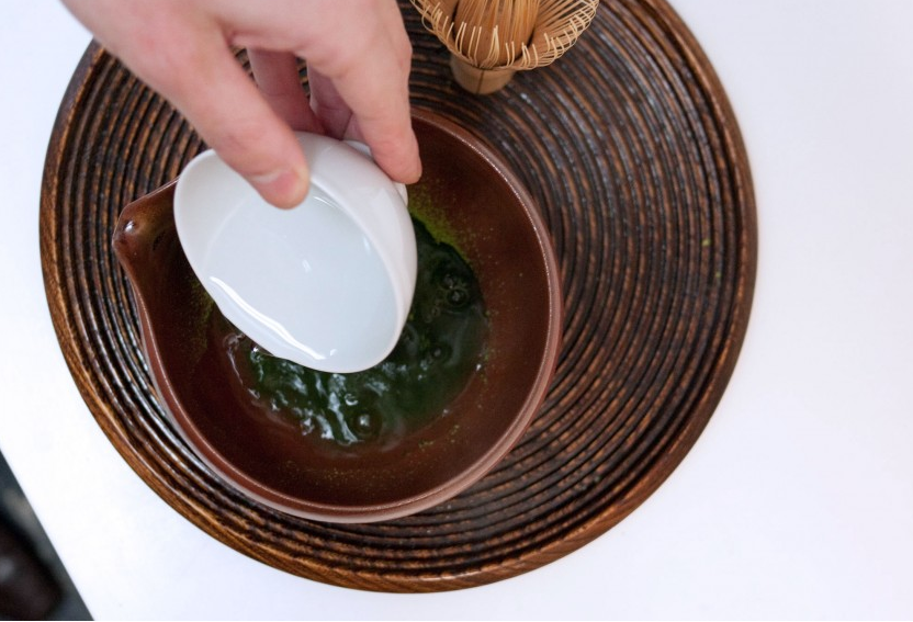 Pour boiling water (about 2 ounces) into a teacup, then let it sit until it cools down to about 180–190 degrees (about a minute). Carefully pour the hot water into the bowl with the matcha powder.