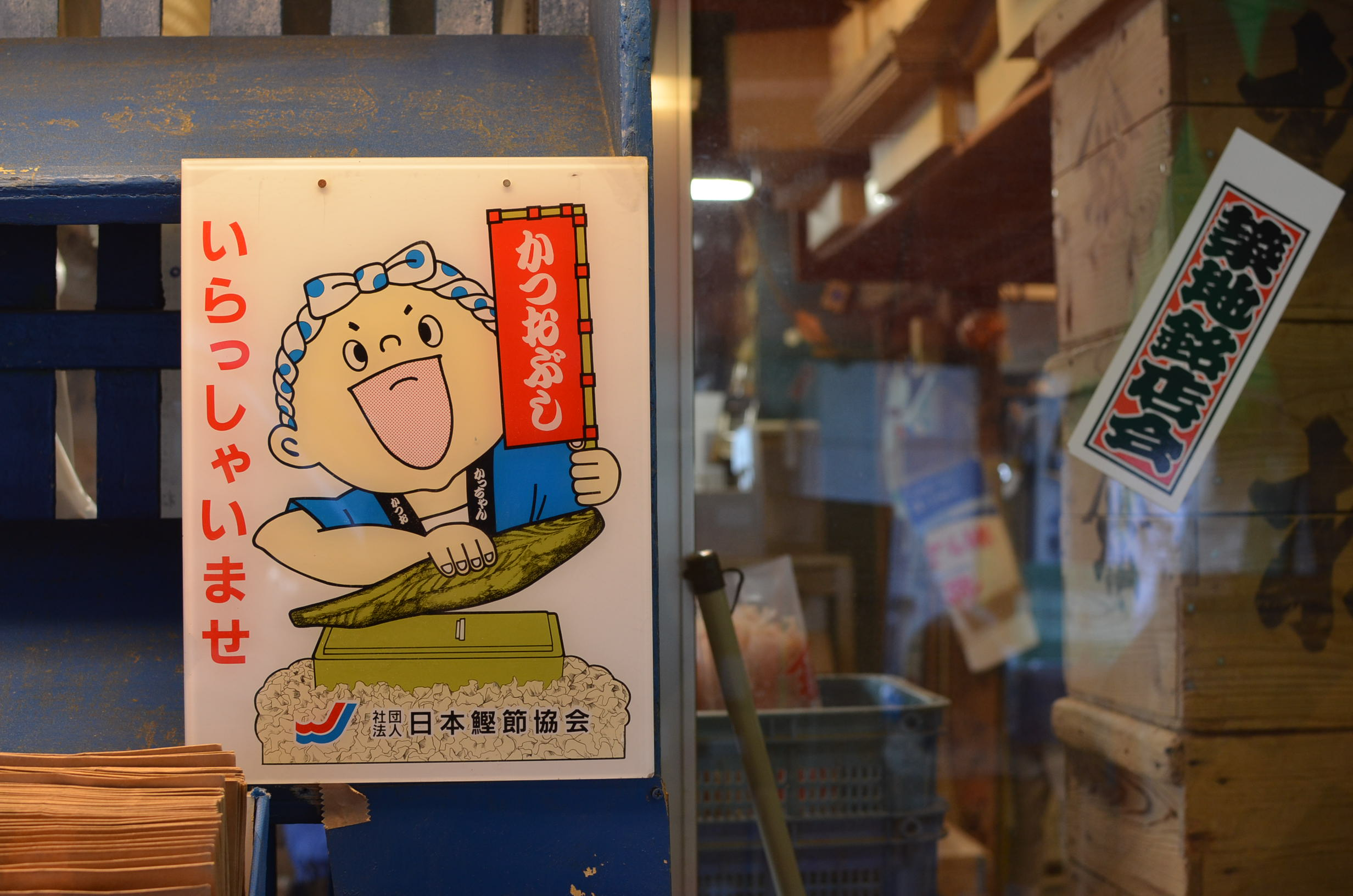 Sign in Tsukiji fish market depicting a chef shaving katsuobushi.