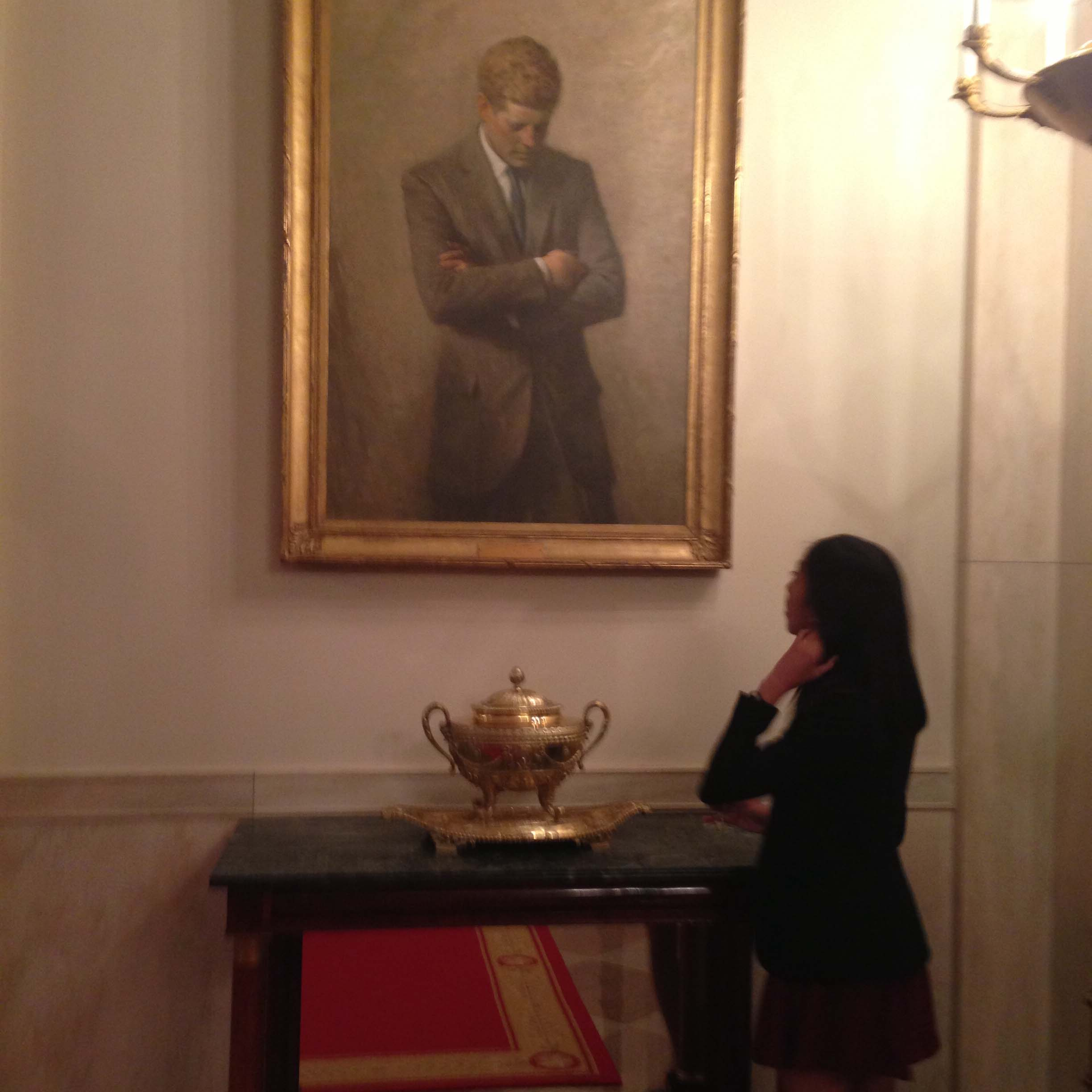 Mentee Jackie mesmerized by a JFK painting in the White House hallway.