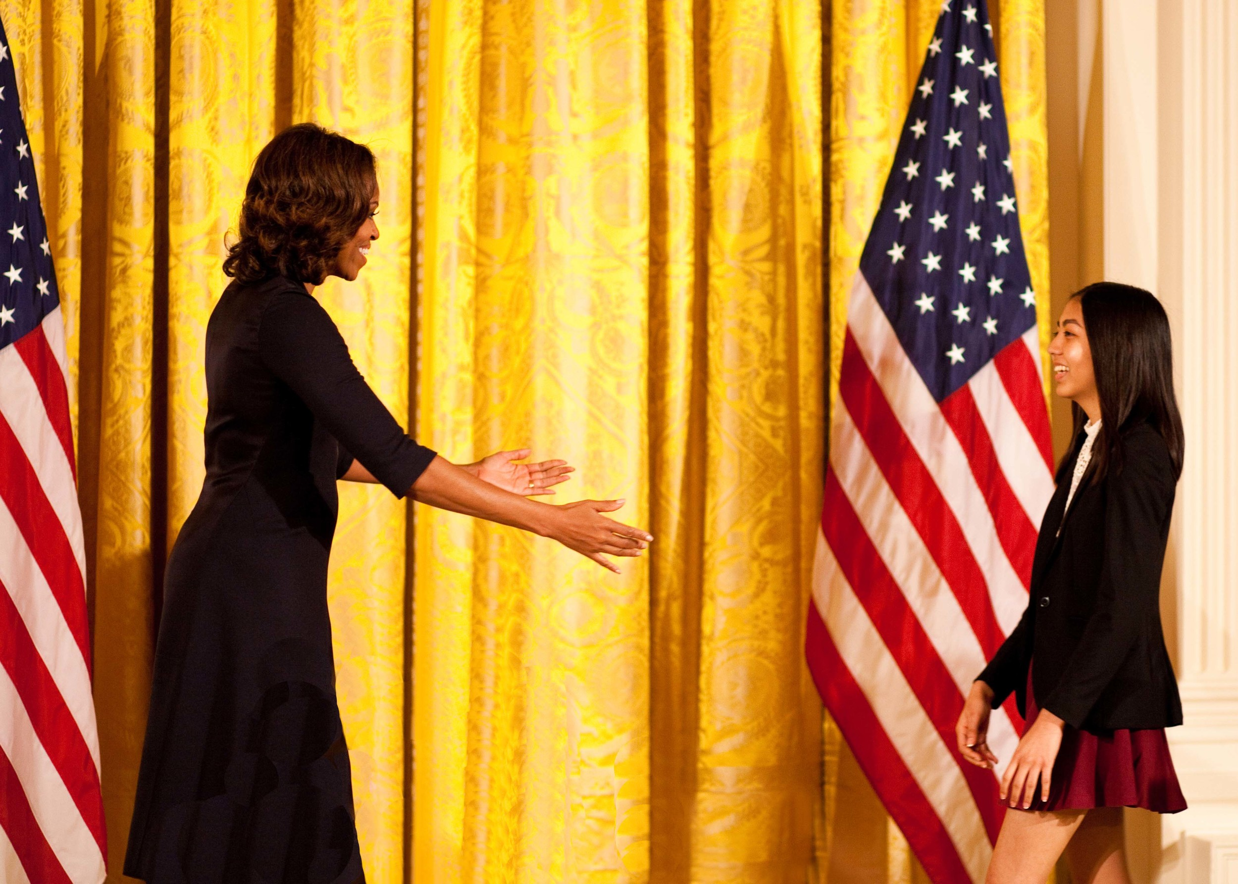 First lady Michelle Obama welcomes WriteGirl mentee Jackie, with open arms onto the stage.