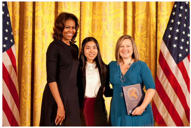 Taylor & 16-year-old WriteGirl participant Jackie Uy accept the National Arts & Humanities Youth Program Award from Michelle Obama.