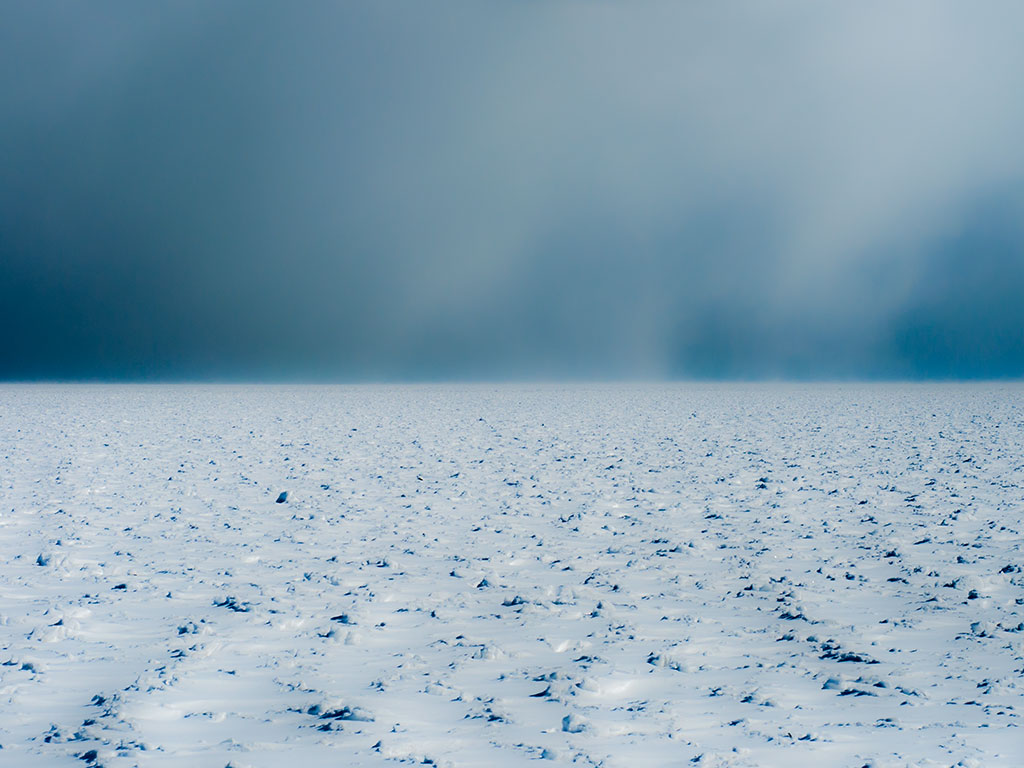 """January's calendar image,""""Storm Crossing,"""" shows a blizzard blowing across the frozen lake last winter."""