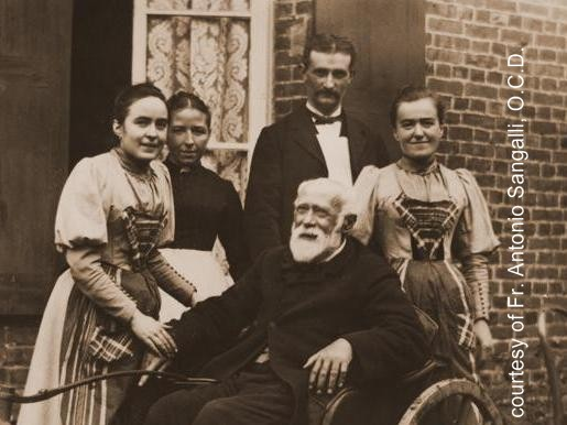 St. Louis Martin, 1892, with daughters Celine, left, and Leonie, right.  In the background, their servants, Marie and Desire Le Juif.