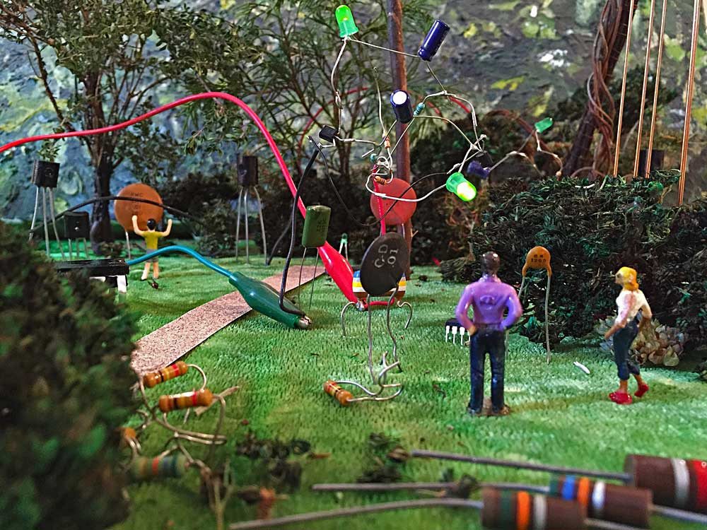 A couple look at the green light emitted by an astable multivibrator living in the Electronic Sculpture Garden. In the background, a child plays with a ceramic capacitor while two transistors look on. Kelly Heaton, November 2015