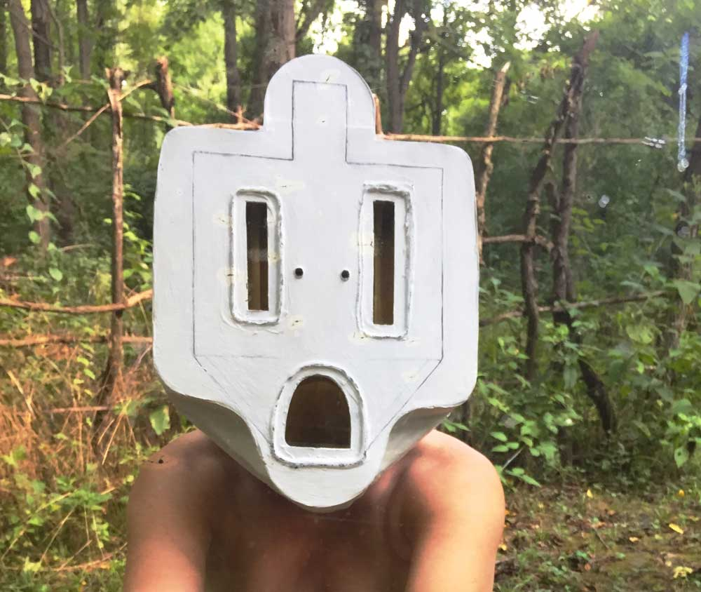 "Socket Mask (Ghost Socket), 2017. Photograph of the artist with her ""ghost socket"" mask made from cardboard, glue, and gesso."