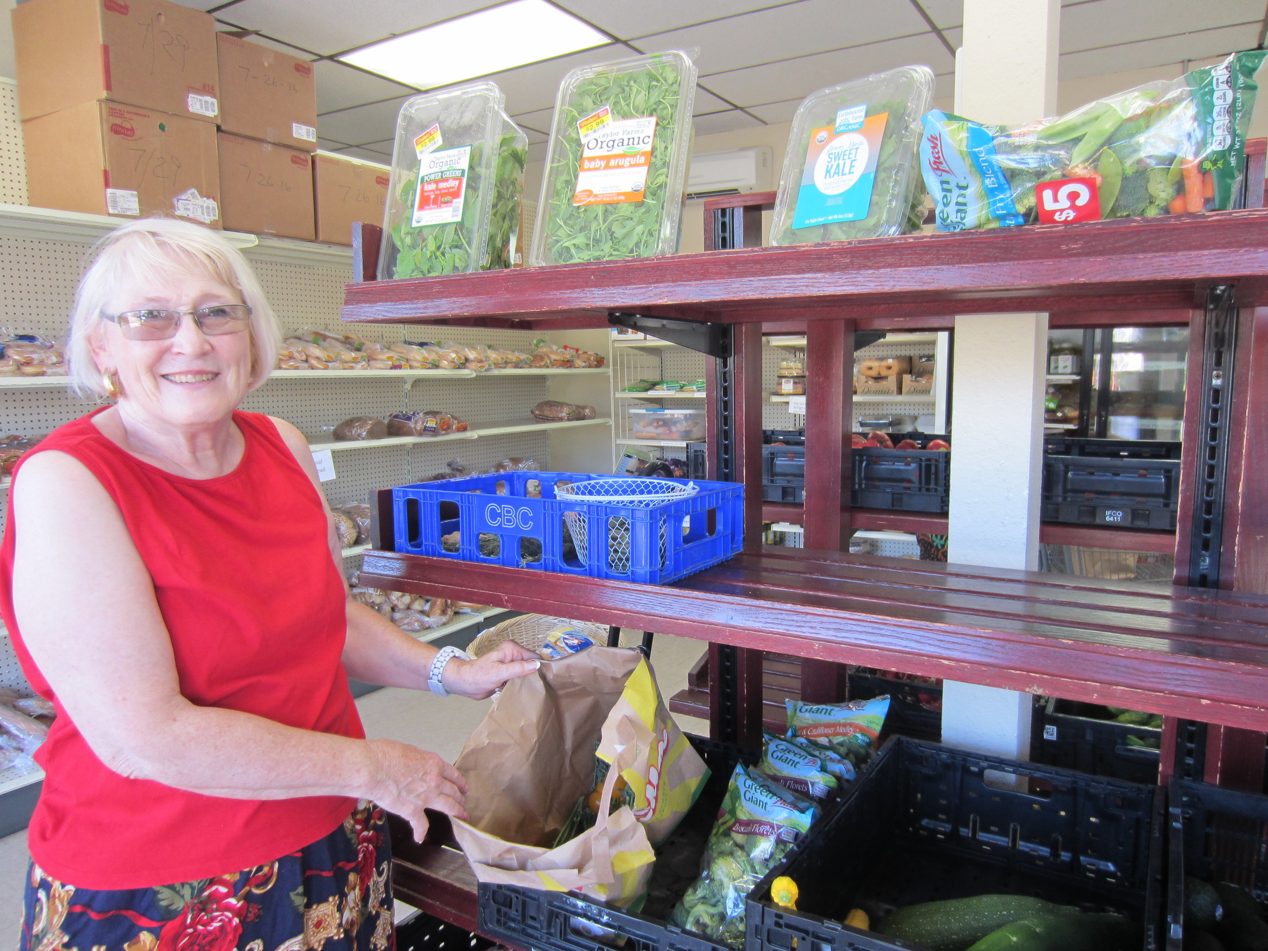 Lynda, a St Johns Food Share member and volunteer, shows off available options at the store.