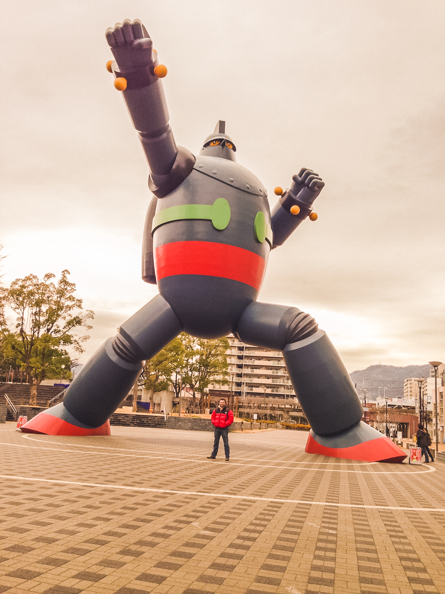 Me standing underneath a monstrous 20 meter tall (59') to-scale statue of Tetsujin 28, next to Kobe's Shin-Nagata station.