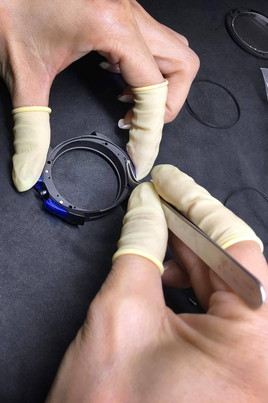 Case details prep  Screws are set up to secure the blue carbon fibre inserts, a striking case detail.