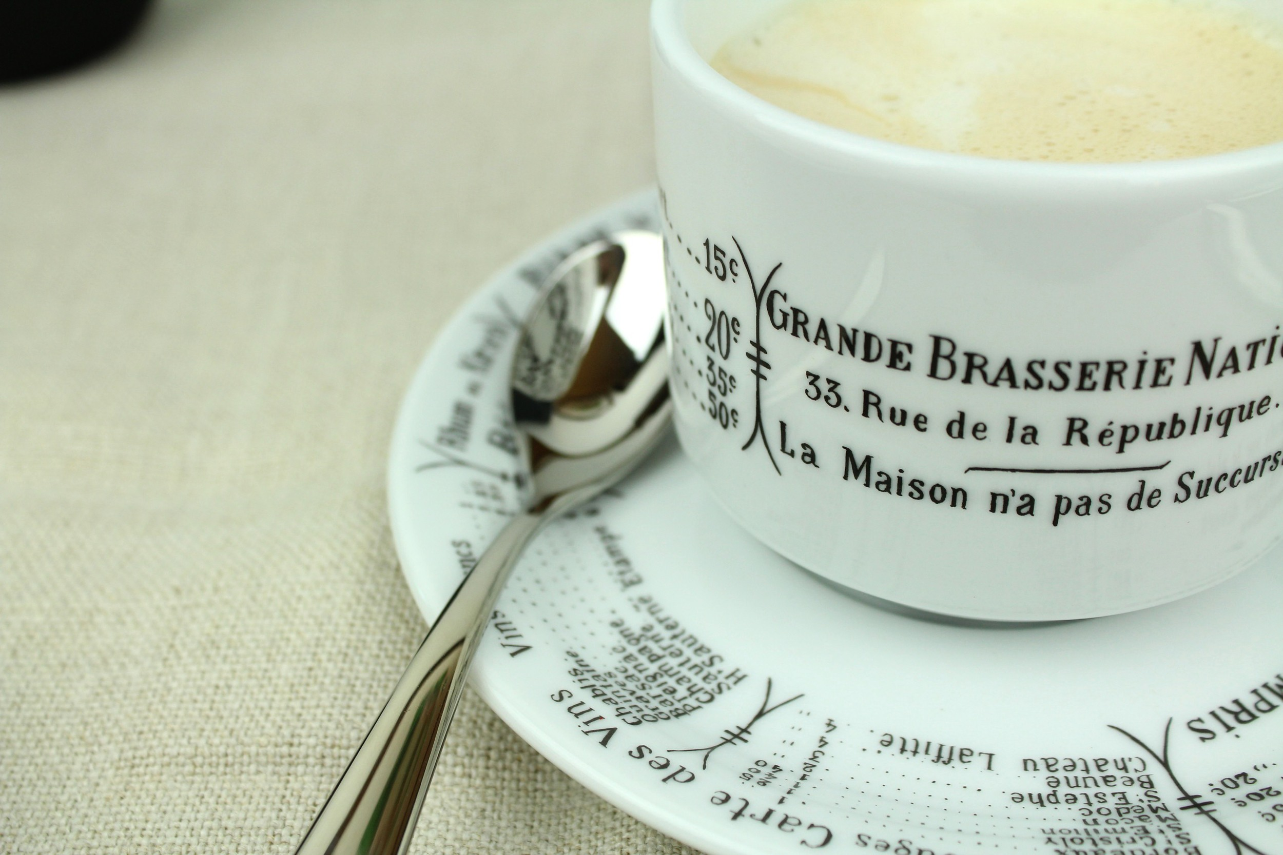 Pillivuyt Brasserie  coffee cup  and  saucer . Alessi  Nuovo Milano teaspoon , Libeco  Napoli Vintage tablecloth in Natural