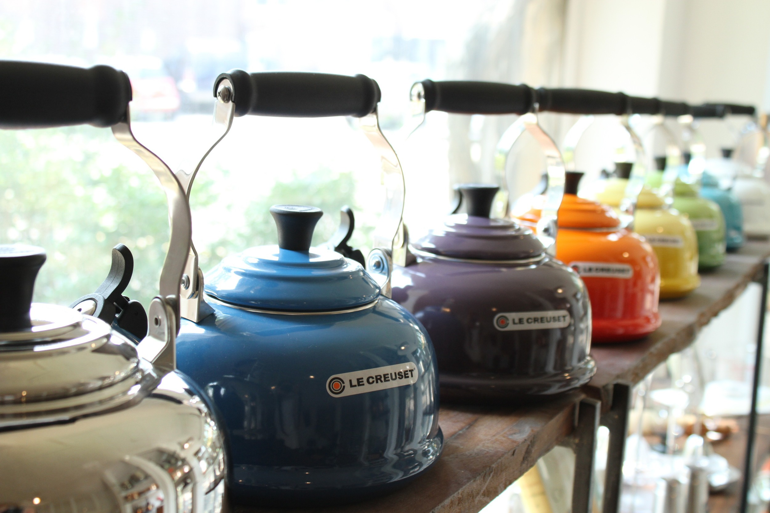 Le Creuset 1.8 qt whistling tea kettles , pictured from front to back in stainless steel, Marseille, Cassis, Flame, Soleil, Palm, Carribean, and White. Also available in Cherry.