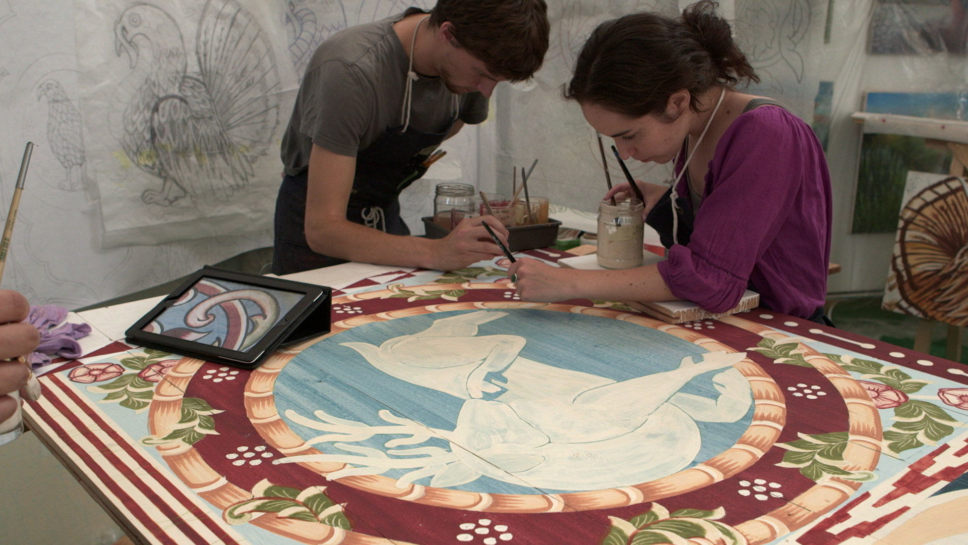 Still 24:  Evelyn Tauben and Jason Bashaw paint the borders of the backward facing deer.