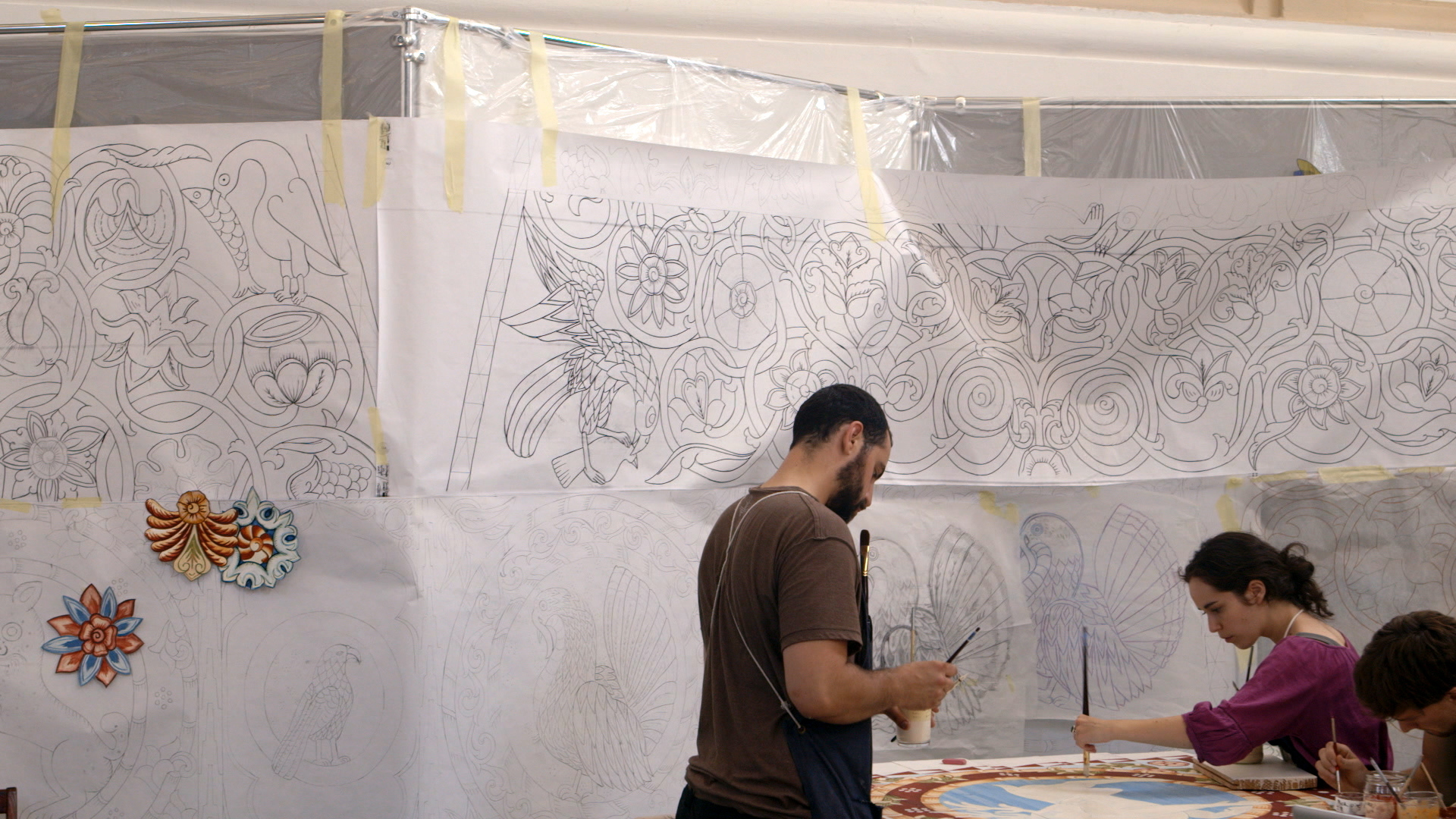 Still 28:  Jason Loik and Evelyn Tauben painting the backward facing deer in front of the tracings for the south dome.