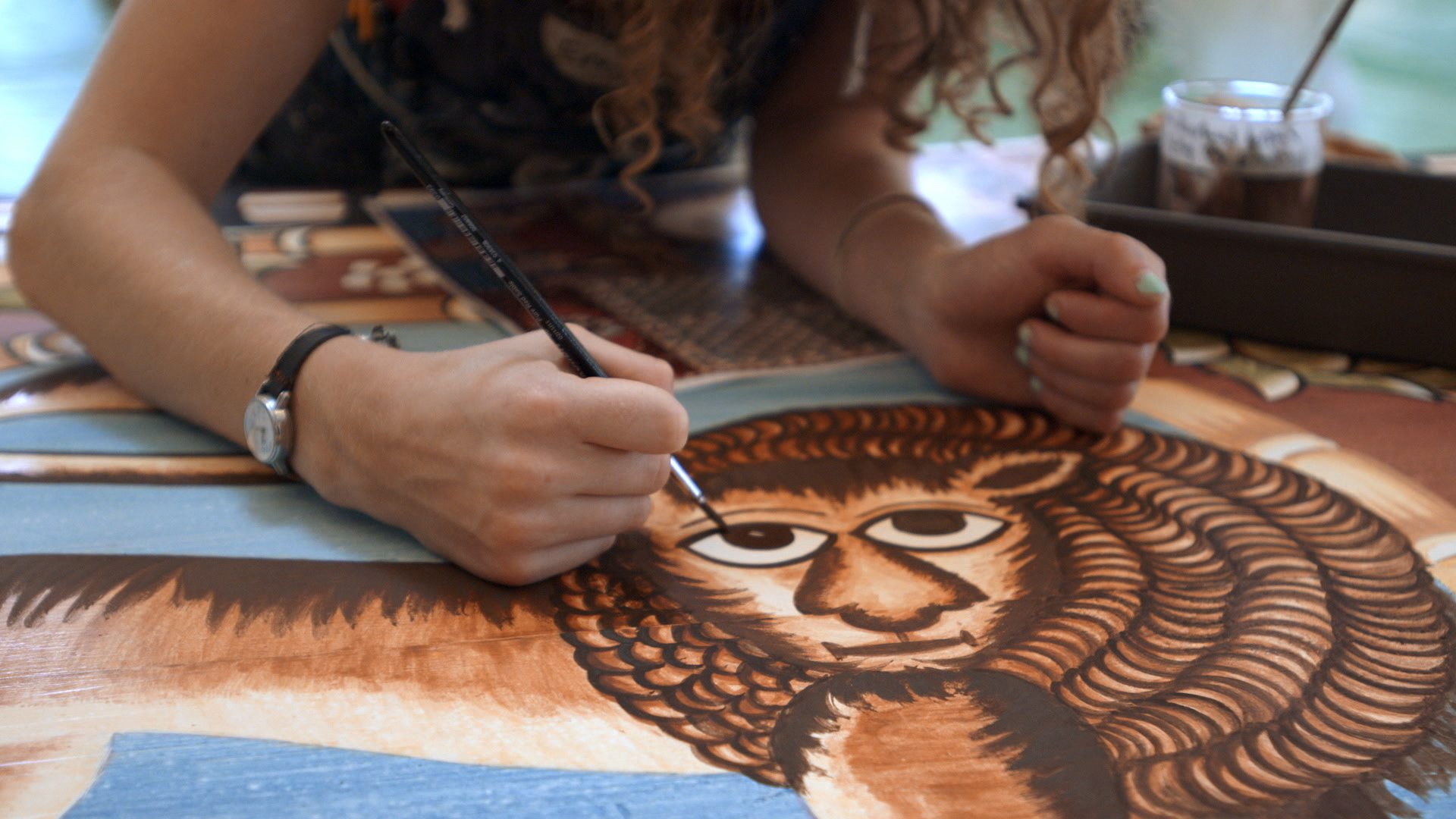 Still 36: Emily White  paints the lion for the east dome panel.