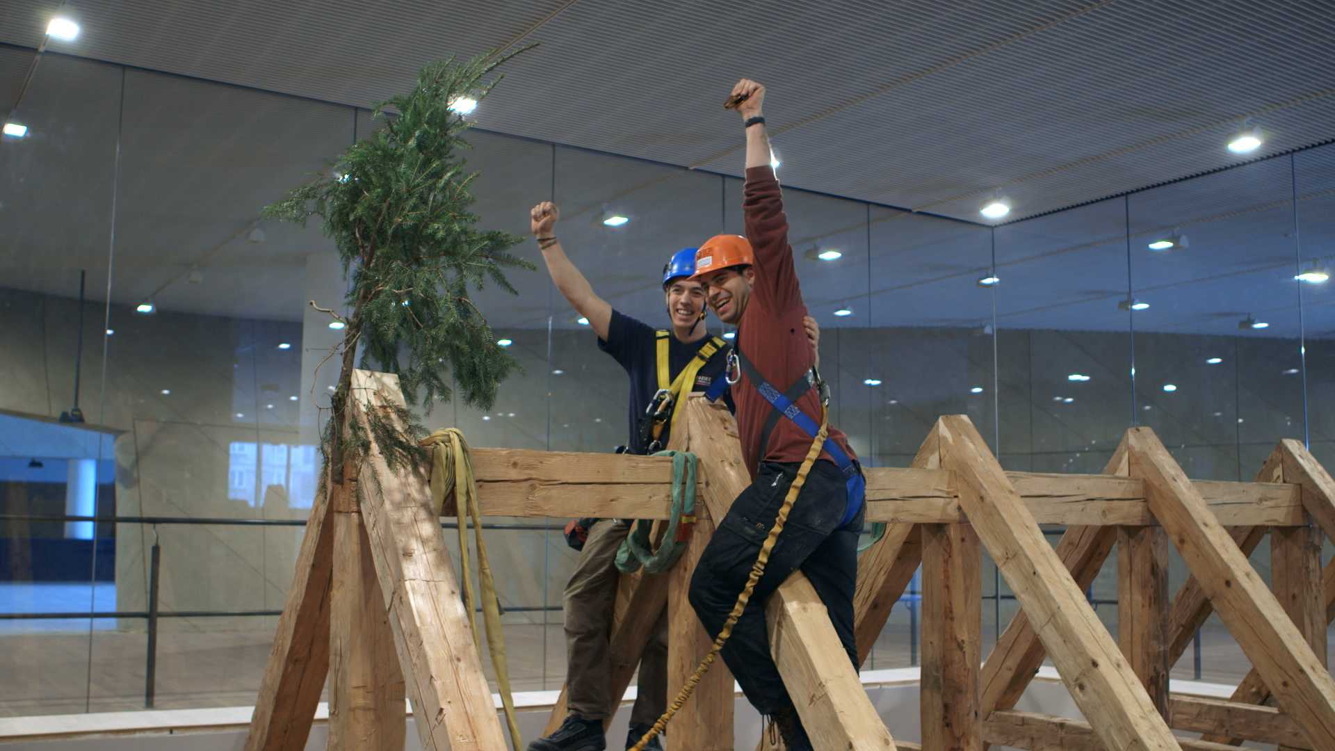 Still 44:  Jason Loik and Jacob Jensen celebrate the raising of the roof by placing an evergreen tree at the top.