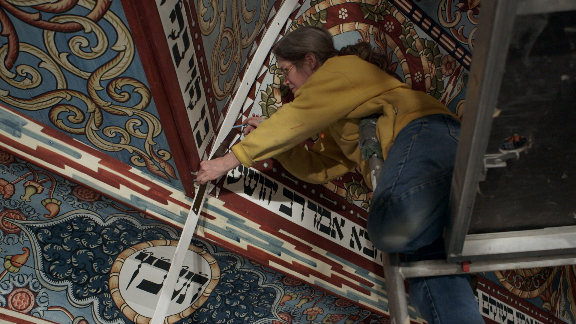 Still 46: Laura Brown measures a trim board made to cover the seams between the dome and pendentive panels.