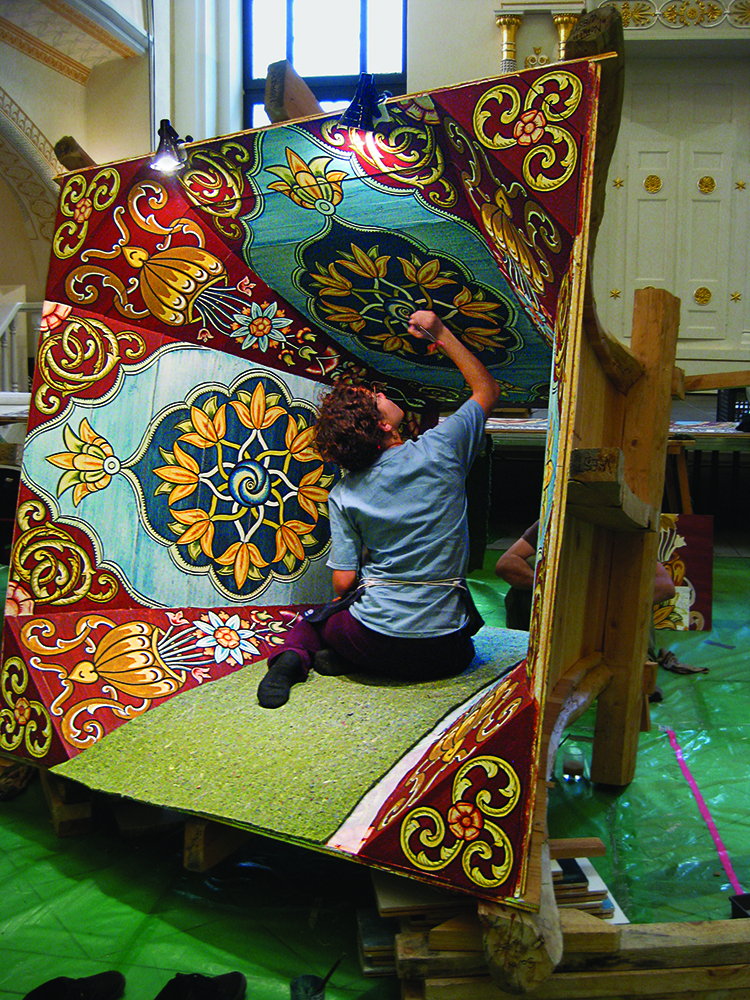 Nestled inside the reversed curved cupola lantern, Savana Vagueiro da Fonseca paints finishing touches on the arabesque.