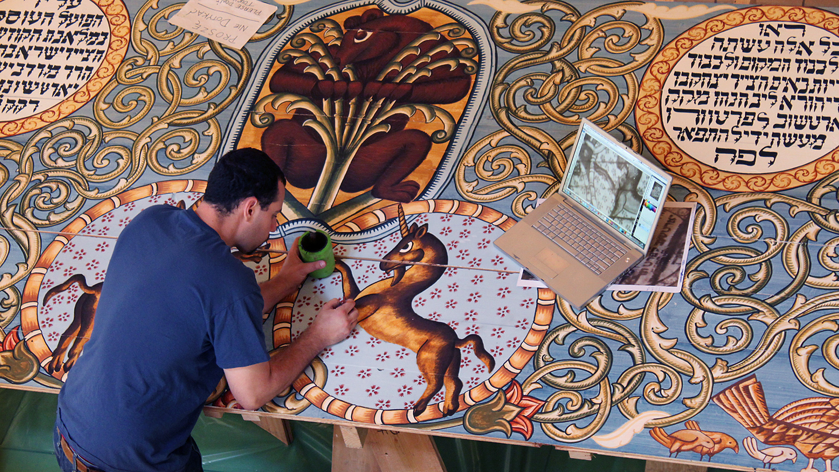 Jason Loik painting the unicorn on one of the Gwoździec ceiling panels.