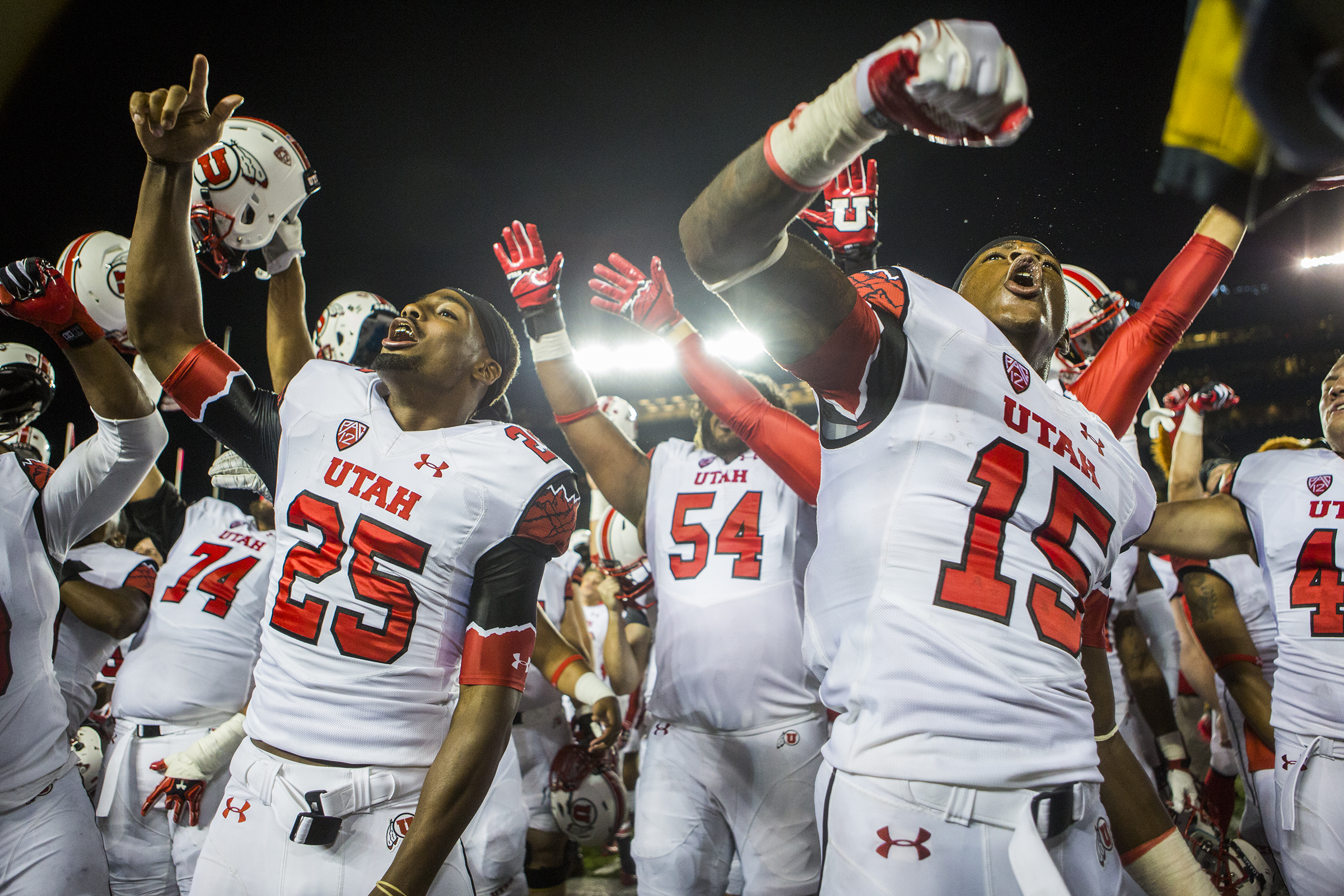 Members of the Utah football team celebrate their victory of 26-10 against Michigan after a 2 hour and 24 minute rain delay in the Big House on September 20, 2014.