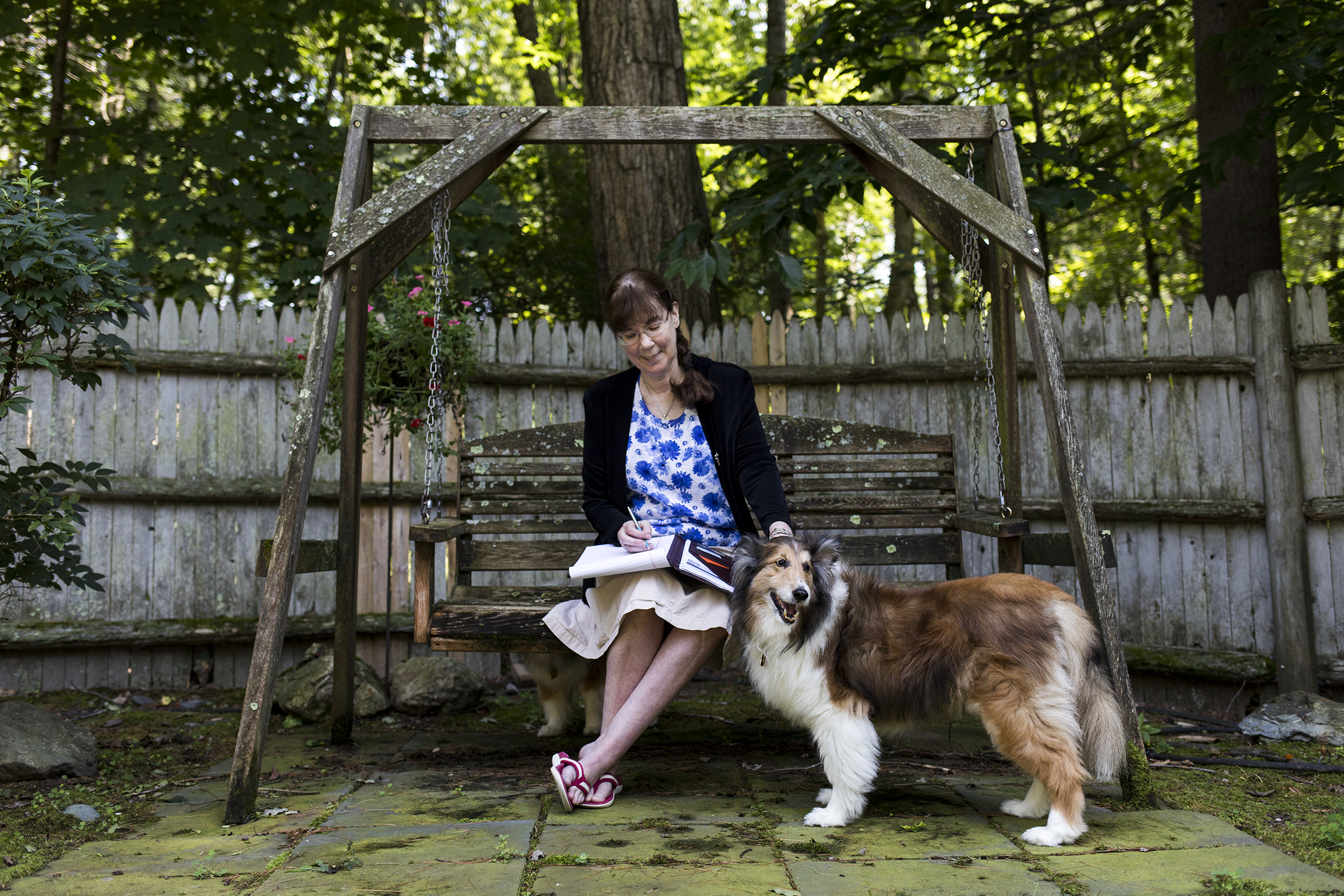 Attorney Susanne Gilliam, of Sudbury, looks over legal documents with her Sheltie dogs Corwin and Merlin outside of her home on Aug. 05, 2018. Gilliam recently volunteered with the Immigration Justice Campaign to act as a lawyer for detained immigrants in El Paso.