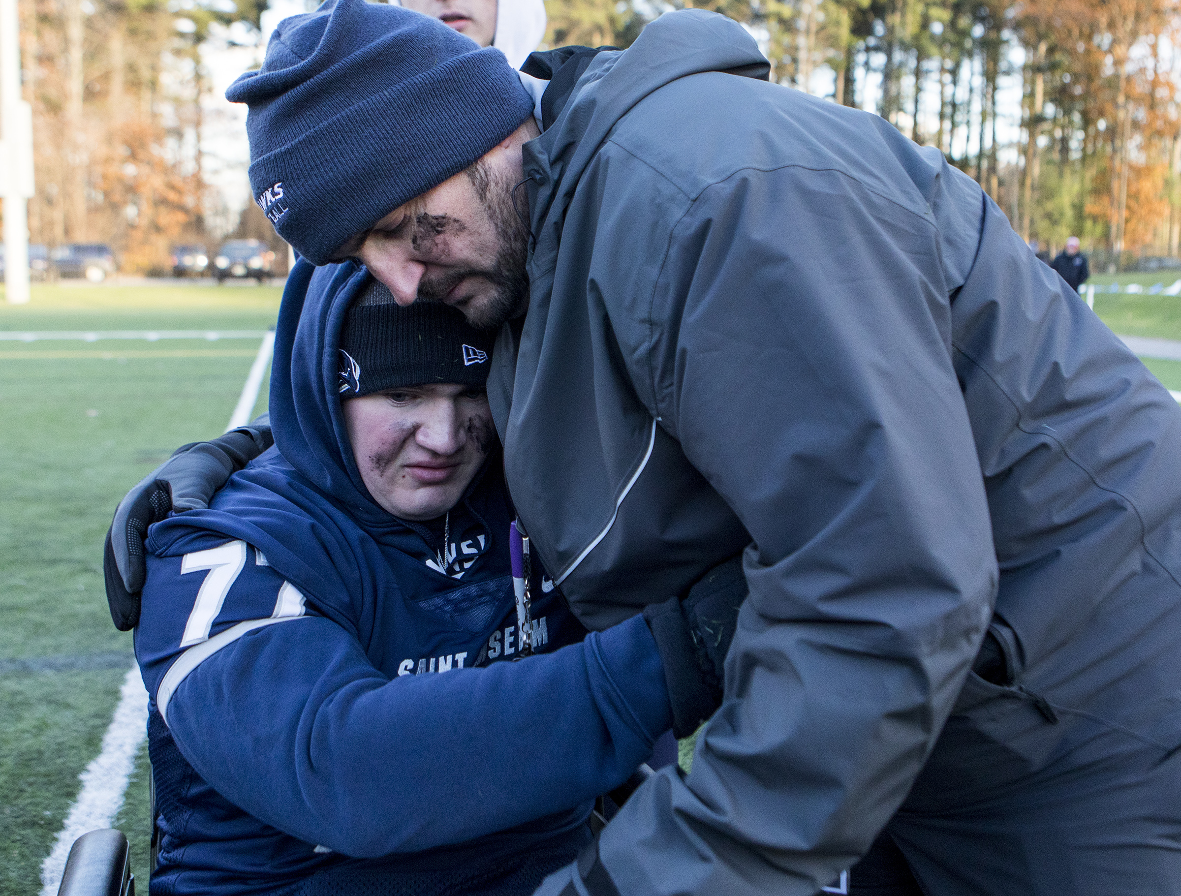 Connor hugs coach Joe Adam after the final football game of the season at Saint Anselm College in Manchester, New Hampshire, on Nov. 10, 2018.